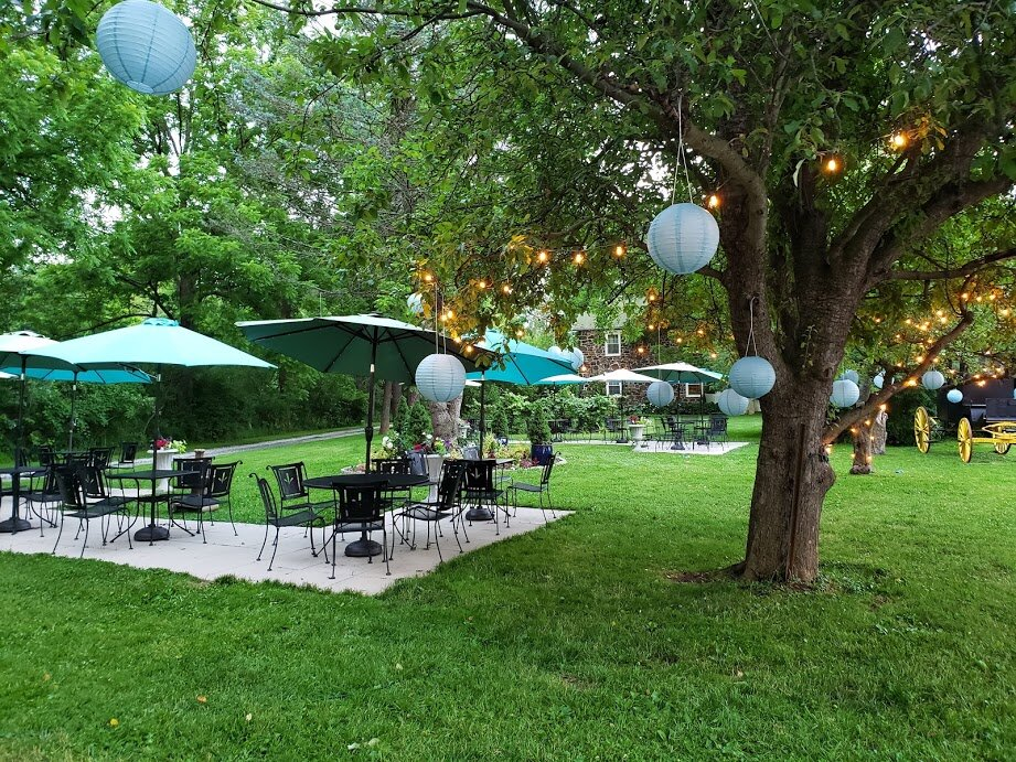 Front Patios & Umbrella Tables - Our wrought iron umbrella tables beckon guests to your cocktail hour under the apple trees in the front garden. String lights glow and the carriage offers the perfect photo op.