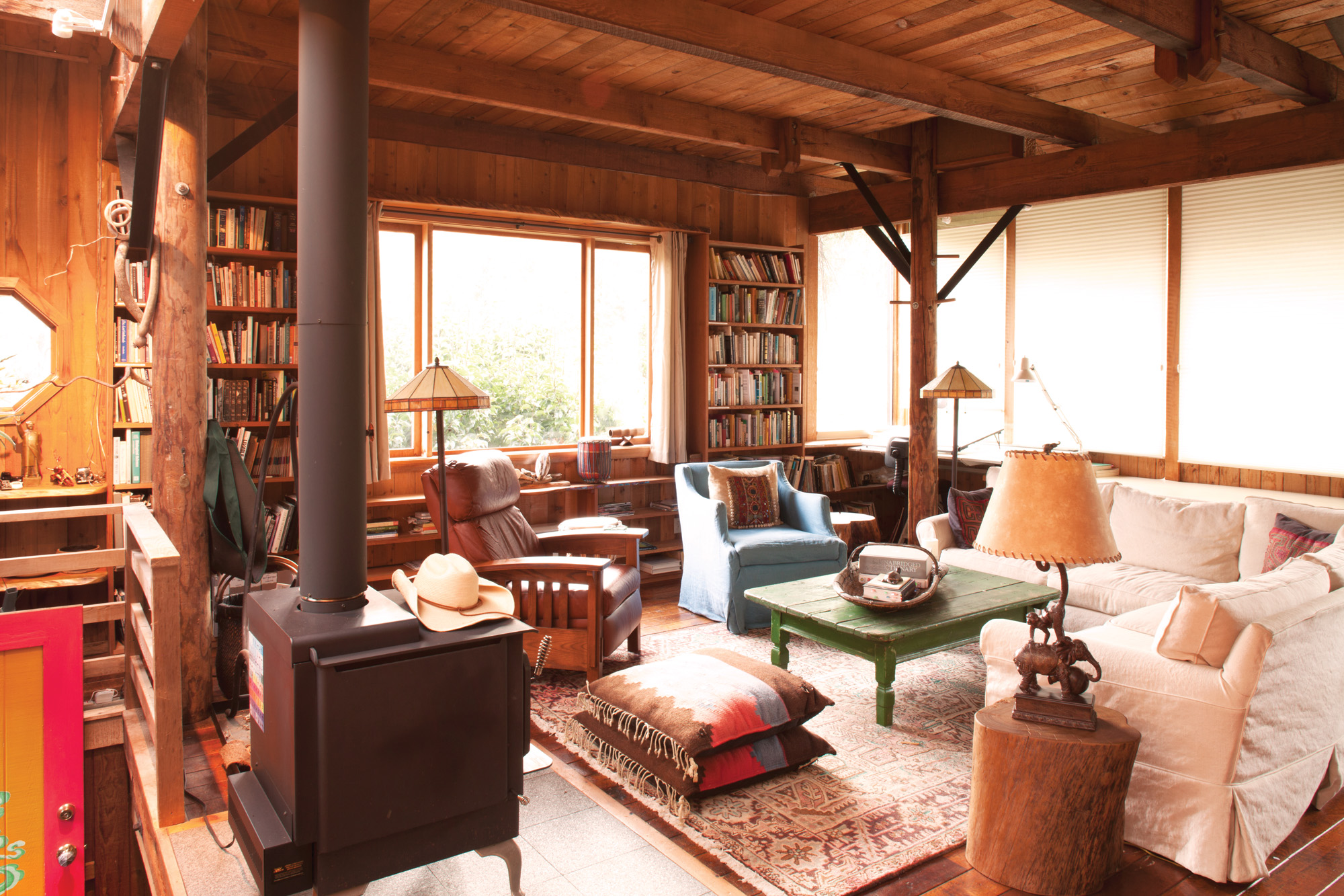 The second-floor living room has high ceilings, walls of windows overlooking the gardens, and a wood-burning stove.