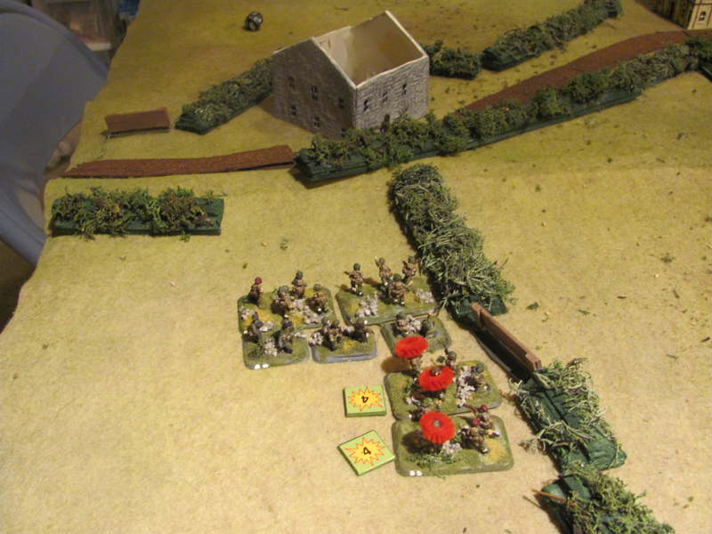 The battered remnants of two British sections watch as their mates move up to try and silence the Germans defending the farmhouse