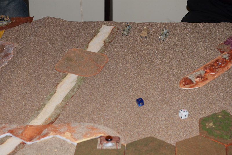 The unfair gunfight. Vickers hiding in the green brush by the white dice.
