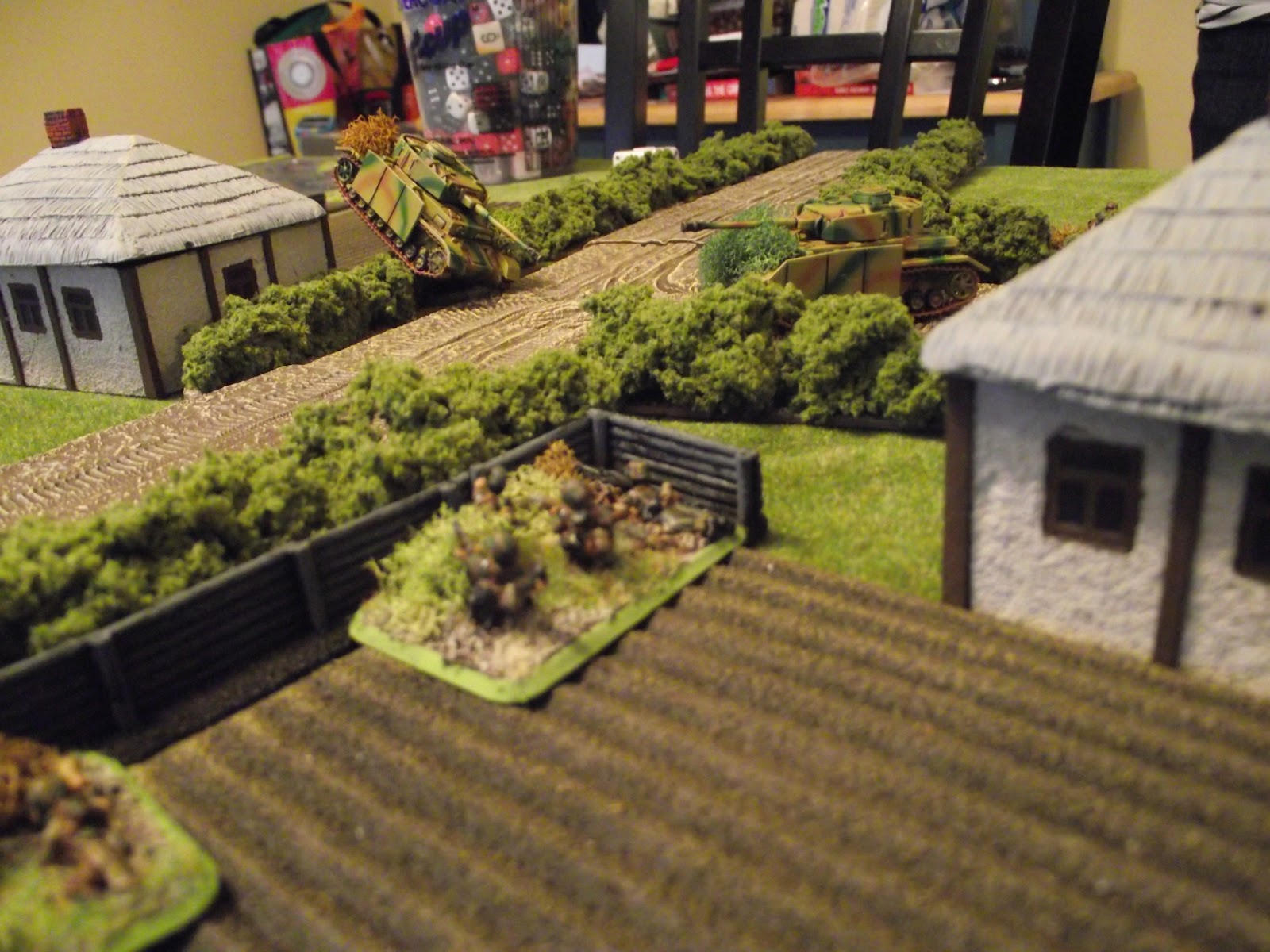 A shot of the German armour moving around. The stuck Panzer on the hedge is bogged down whilst trying to cross. The other is starting to look for targets.