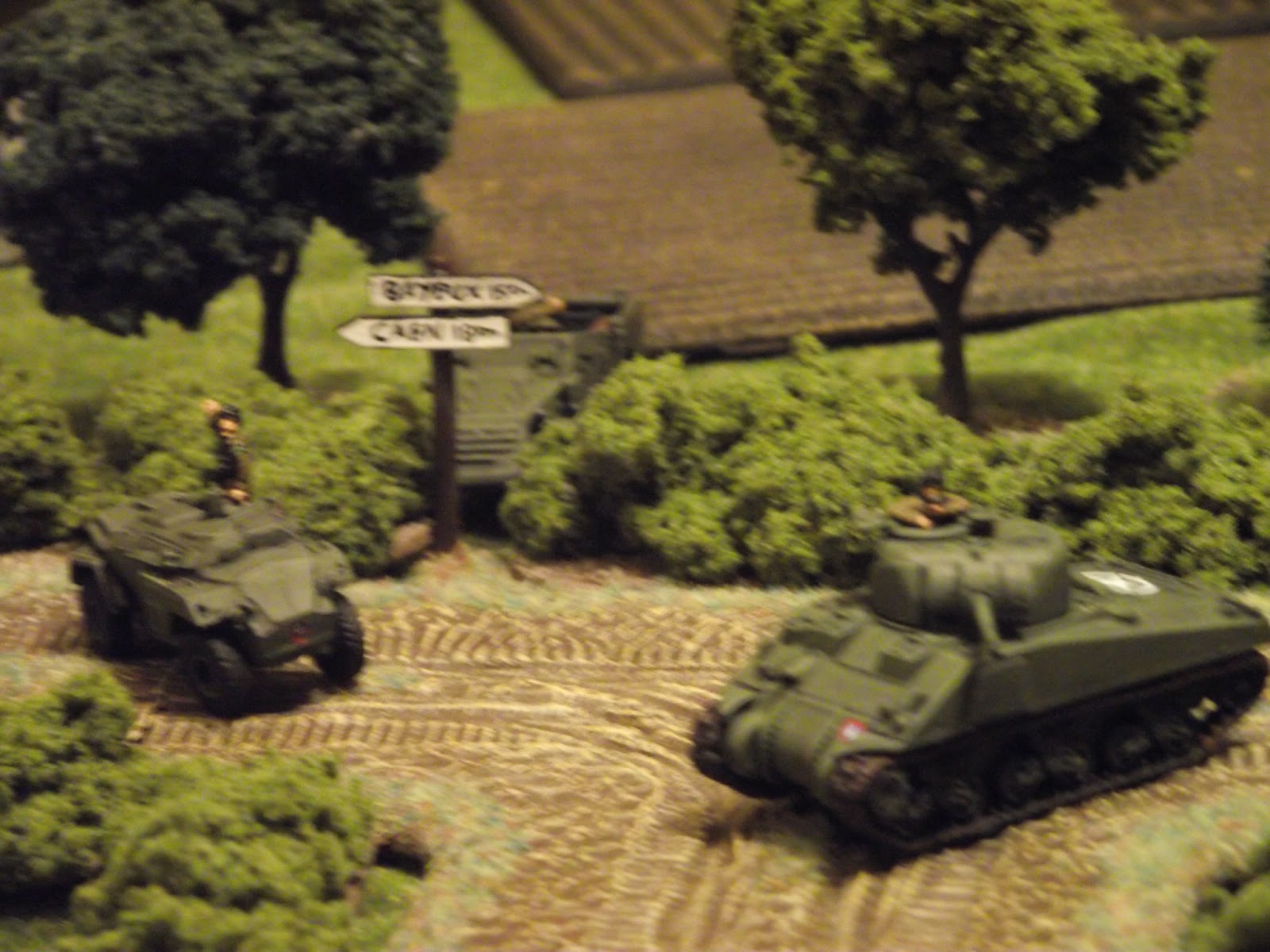 The British cannot seem to spot into the town, so the armour decides to force the issue by advancing around the bend.