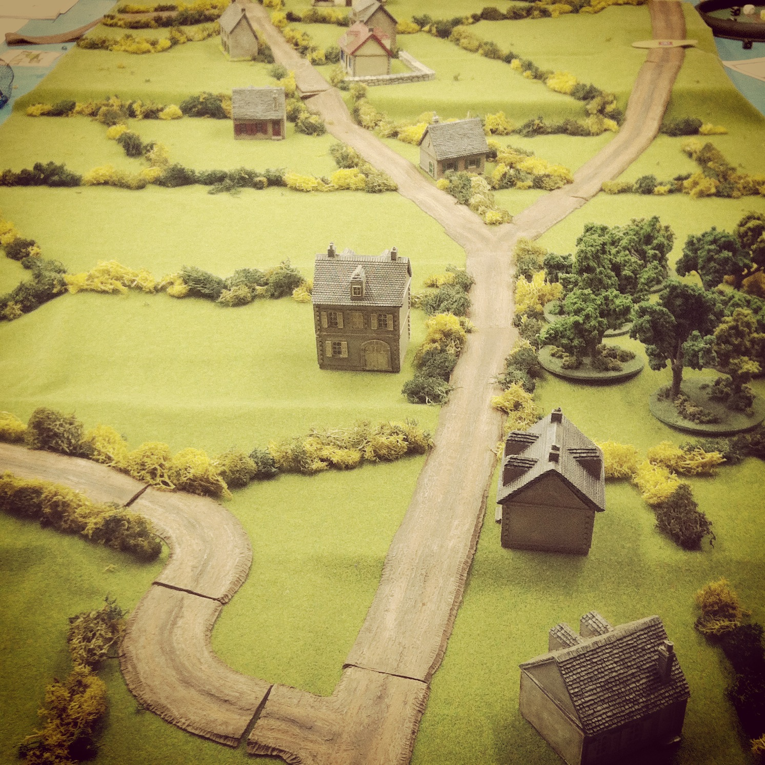 Scenario set-up with two small houses as objectives at the middle of the table set amid rolling hills, small farmsand thick bocage