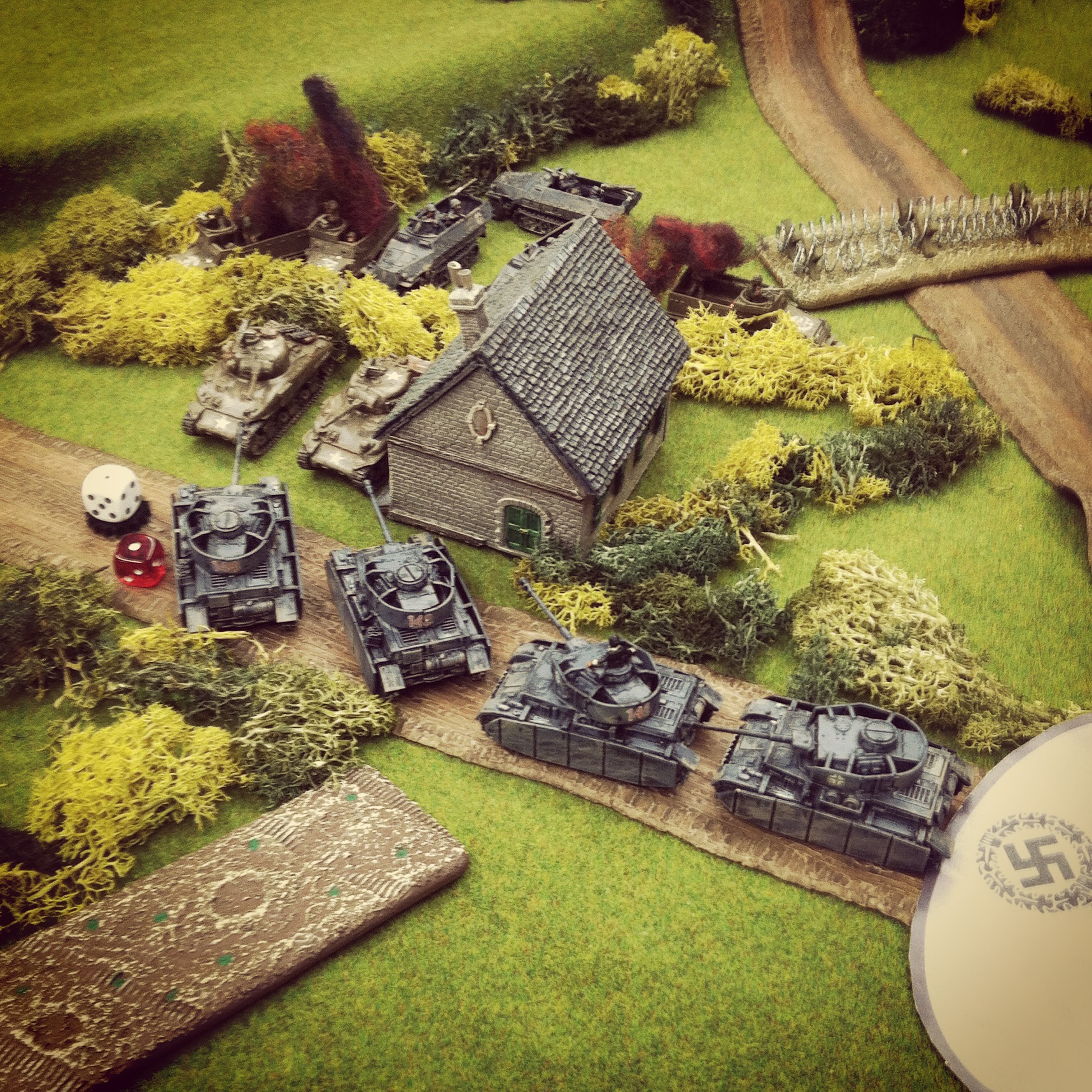 The German Panzer IV column exposes two Shermans behind a farmhouse