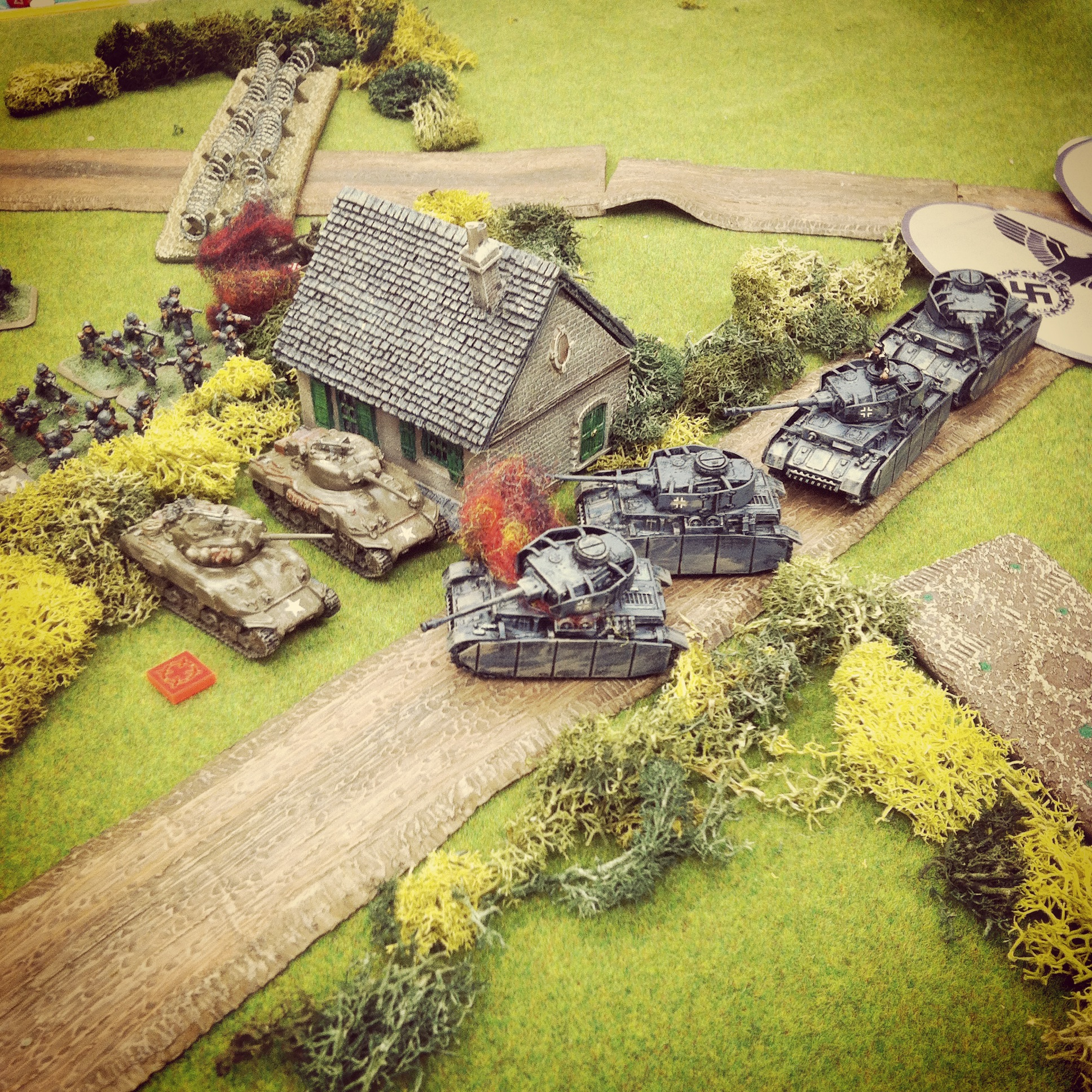 The lead German Panzer IV is destroyed, blocking the road