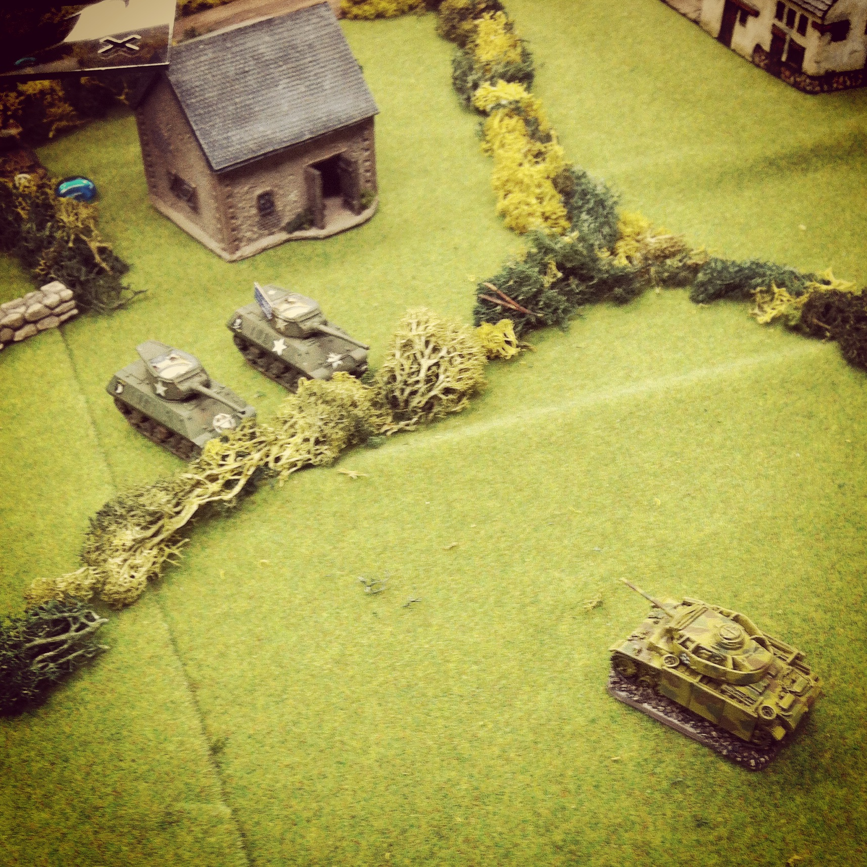US Wolverines take aim at a German Panzer III flame tank in the open