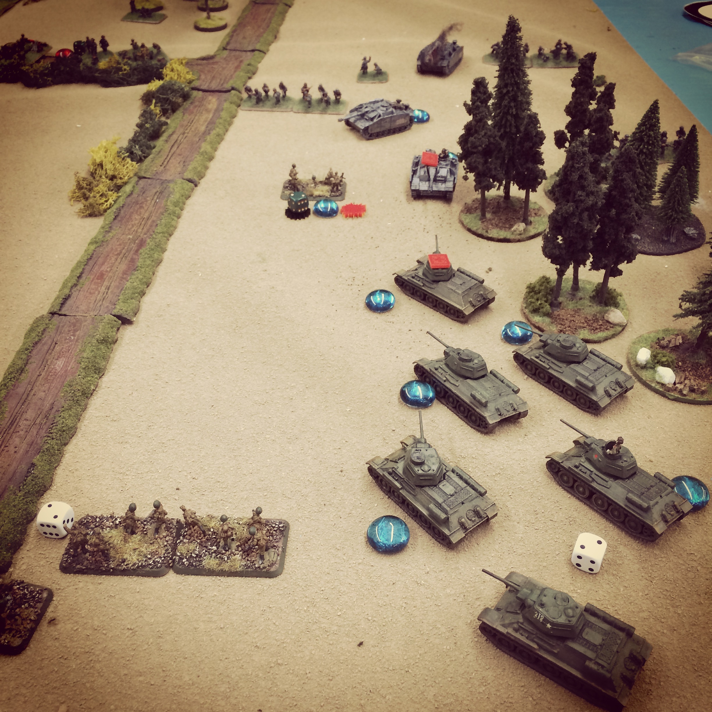 T-34s and StuGs duel at the edge of the forest as infantry begins to take heavy casualties on both sides