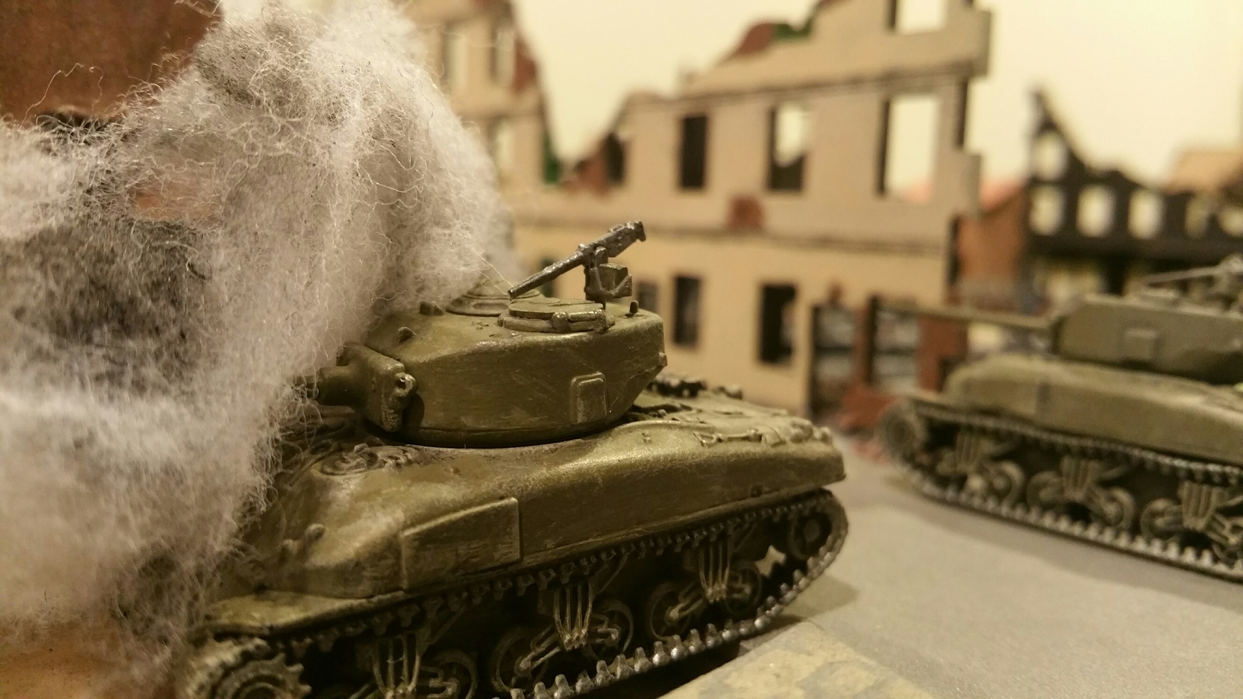 Big gun Sherman burns in the center of town after dueling with the Pz IVs.