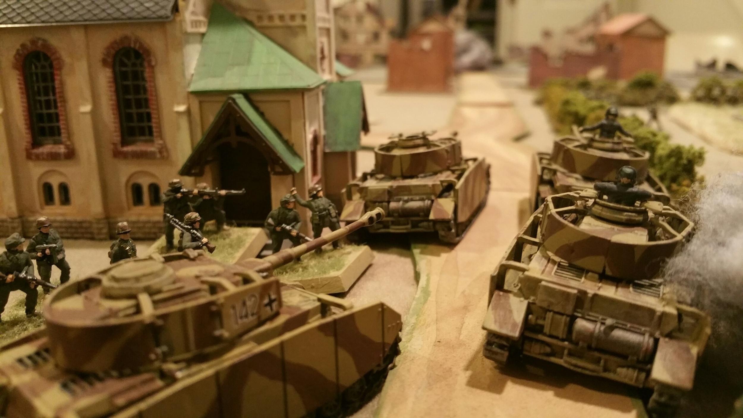 Burning German Panzer IVs stack up after bazooka teams and Shermans plug the gap.