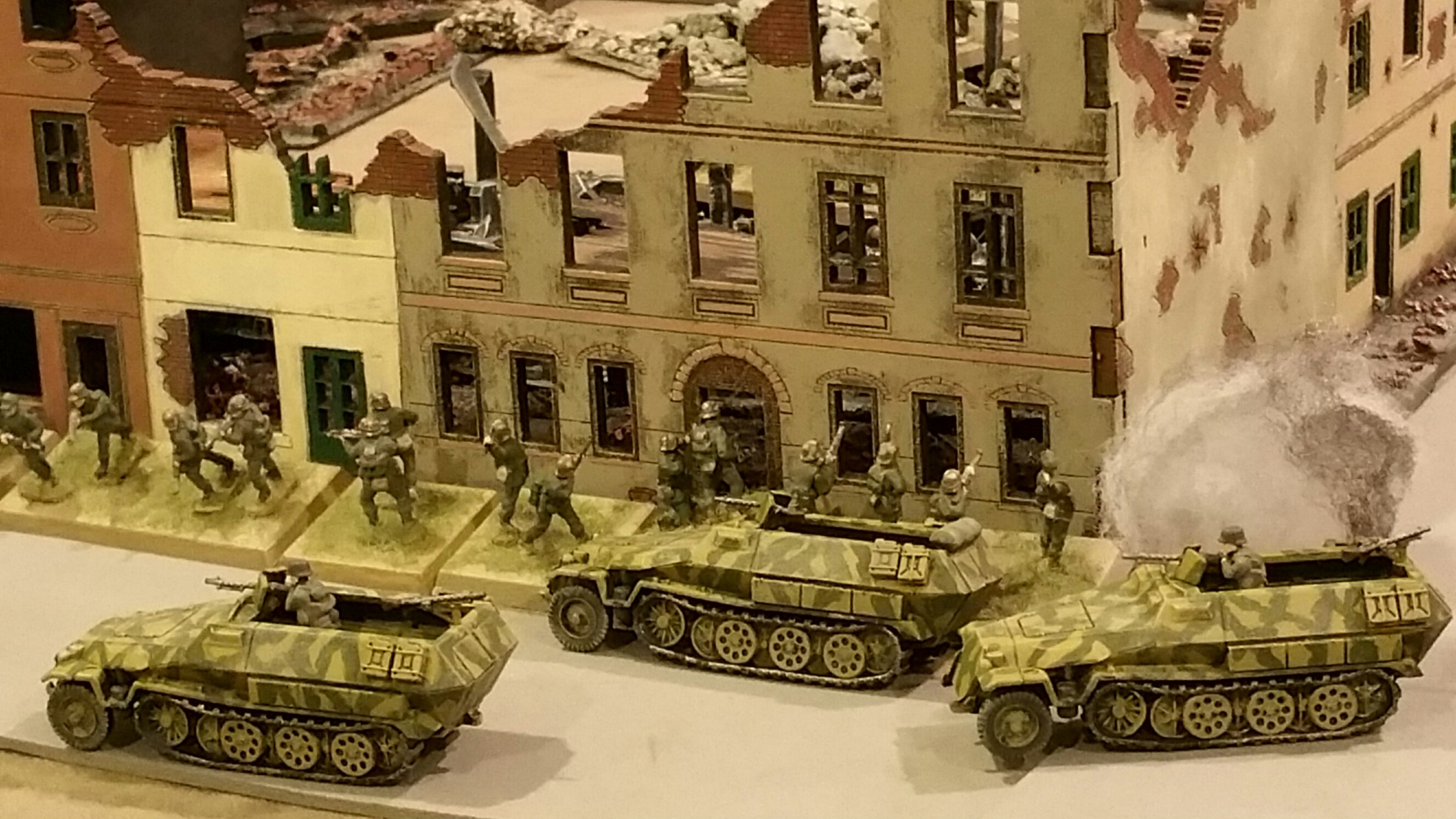 The German infantry pushes in the center. After a bloody repulse of one platoon in close combat, 2 others push into town. Armored Panzer grenadiers disembark and begin to push the remaining G.I.s in town.