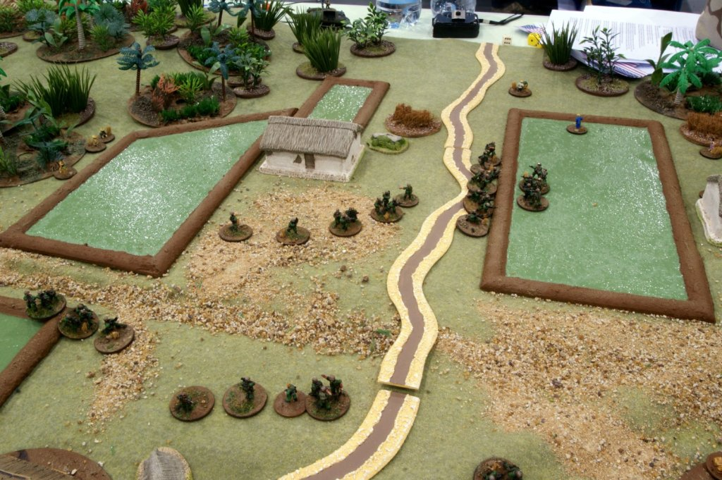 US troops are beaten back from the eastern end of the village, hunkering down by a paddy field's berm.