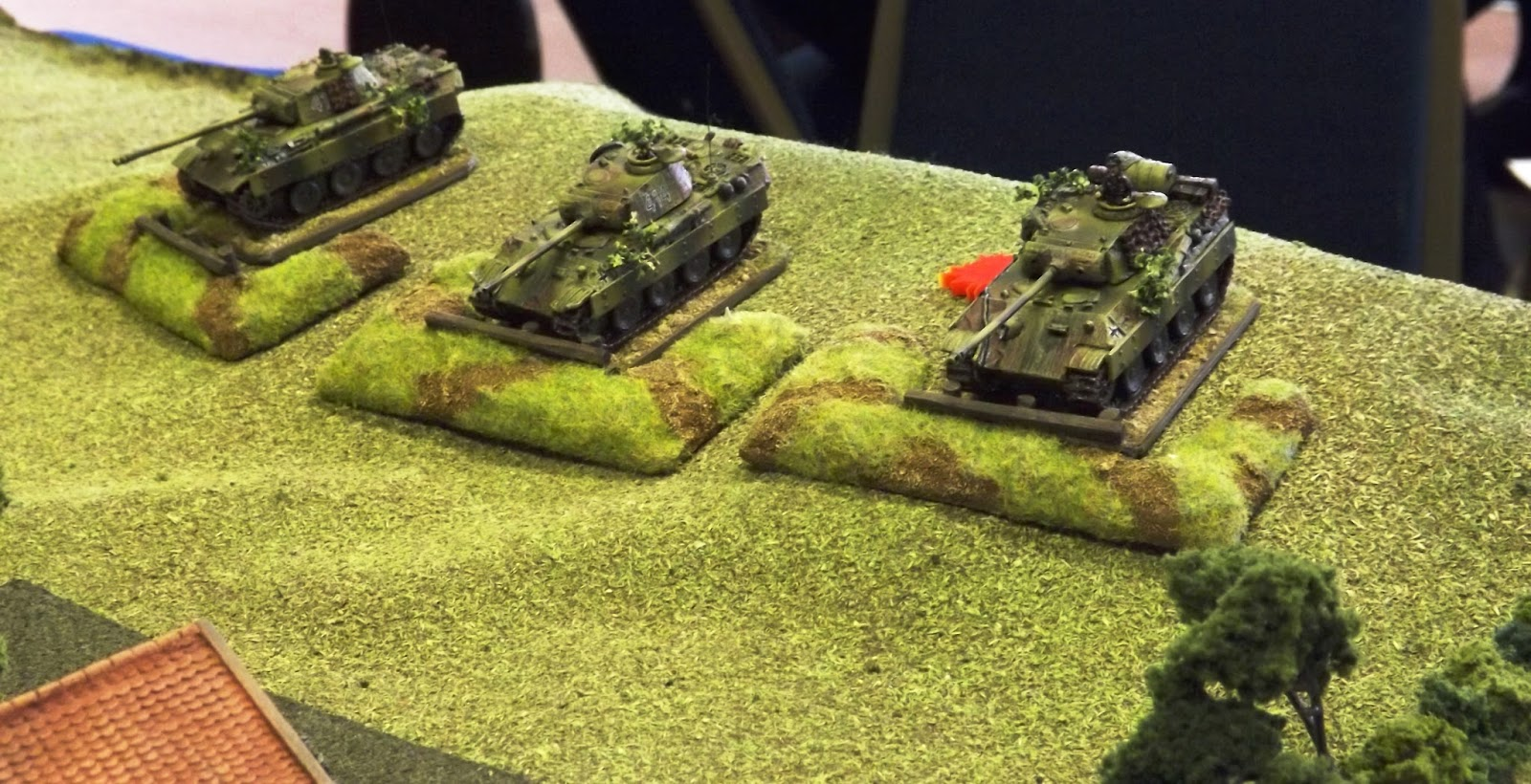 Panthers dug in above the farm open fire and take return fire from the lumbering British tanks