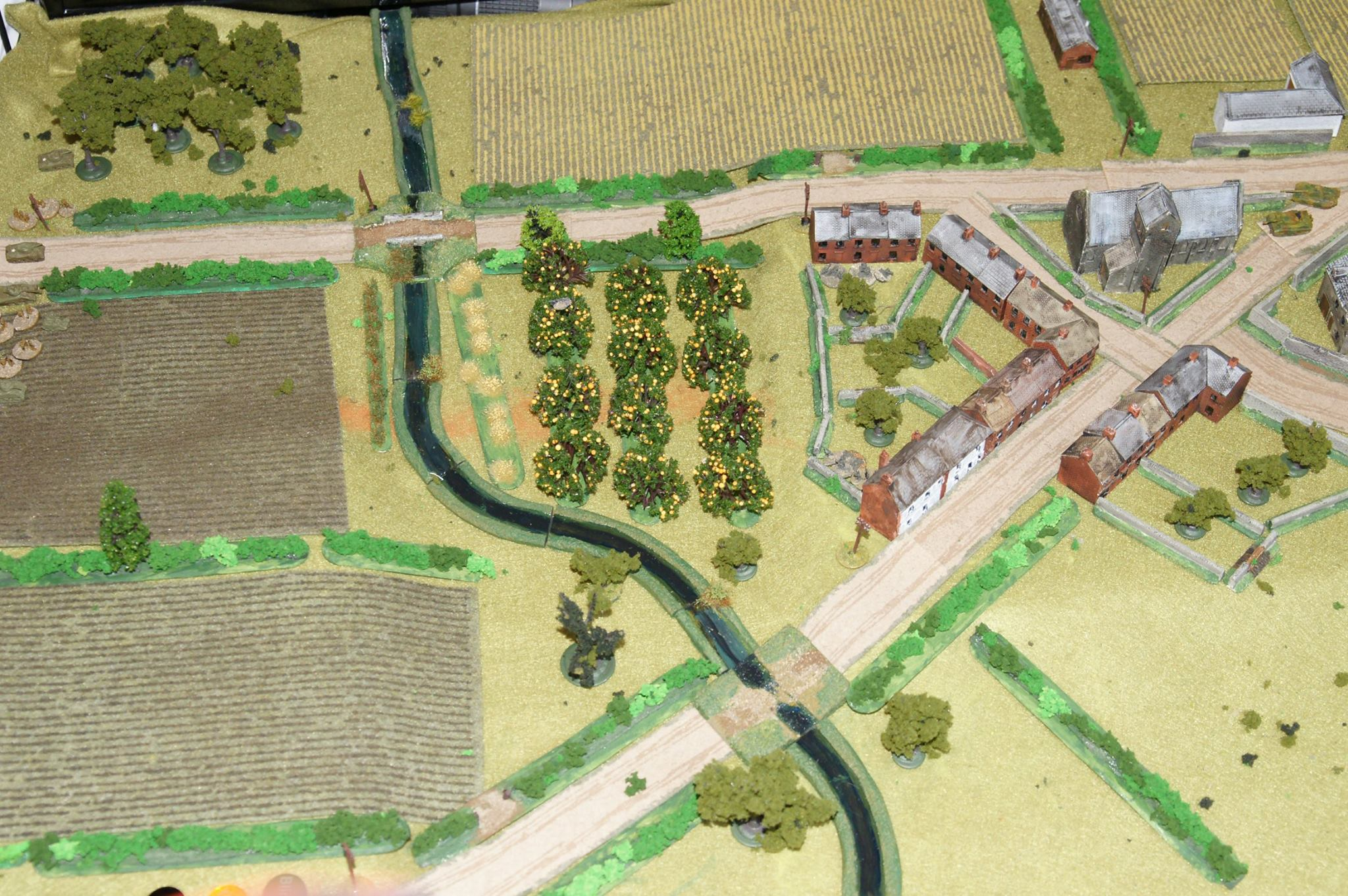 At the start of the battle, the Tiger and Panther lurk at the cross roads and two squads are deployed covering the bridges.  The British plan is to hit both bridges simultaneously, thereby not allowing the Germans to concentrate their meagre initial forces. Fireflys at the back to try and snipe the German big cats. It's a solo game, so nothing is shown under Blinds.