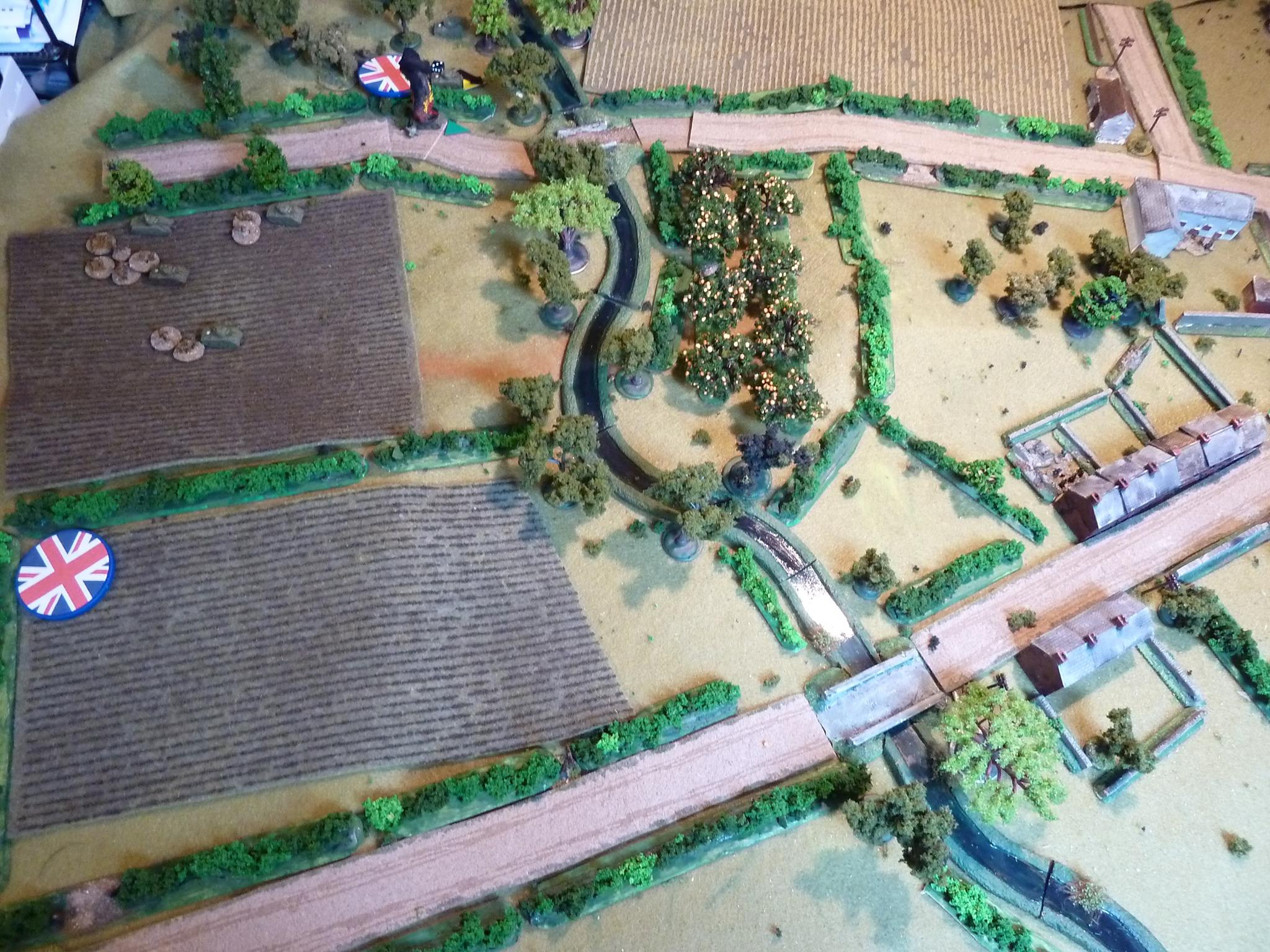 First blood to the Panther, just off cam on the right:  a smoking M4.  The Canadian second force heads across the ploughed field aiming to cross the river and find cover in the orchard. Quickly spotted by a German sniper tied to an apple tree. Crossing the ploughed field is slow going and the sniper further slows the Canadians with plenty of shock and pins.  The Canadian FOO and Vickers head for the high ground on the left.