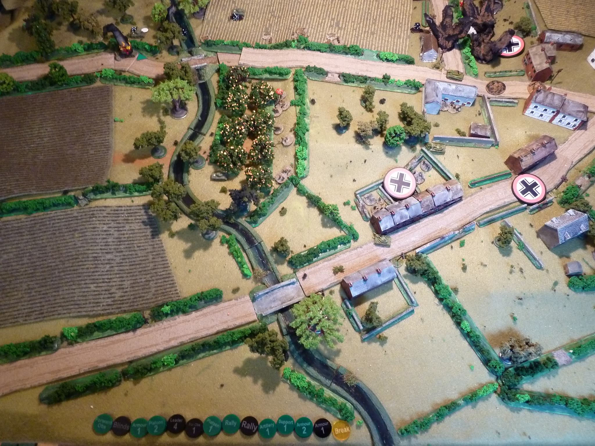 The two German big cats pin down the Sherman platoon in the wood top left, bailing a Sherman and knocking out the Firefly in a duel.   The FOO switches the 25pdrs to the Panther: again no effect.  The Canadian 1st infantry platoon are moving up the hedge line at the top and the 2nd has crossed the R.Dives and pushed through the orchard to the hedge line centre with more Shermans in support.  A couple of Pz IVs and squads have arrived and reinforced the position in centre around the row house in the centre.