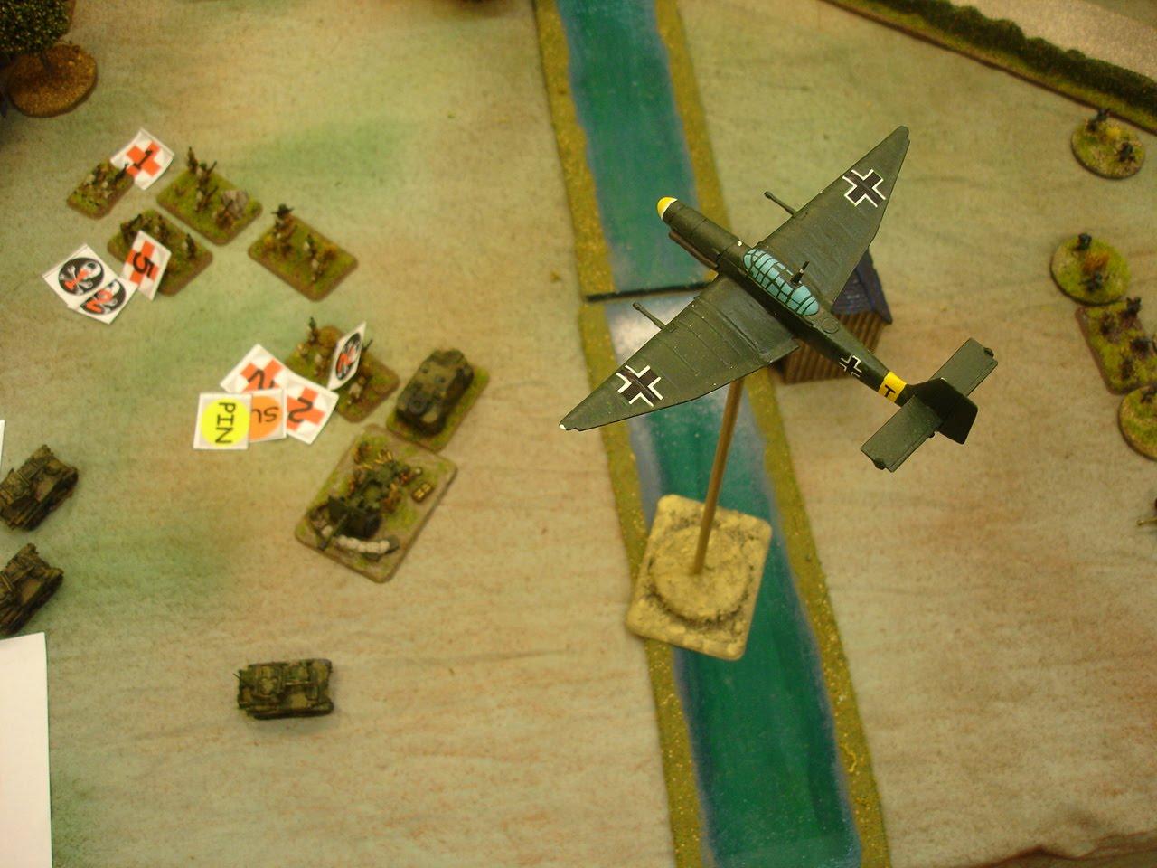 A Stuka divebomber prepares to strike British infantry
