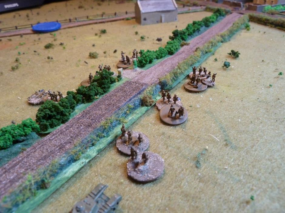 While the British #2 & 3 platoons move forward, the Germans are holding fire until the British squaddies are within effective range.     There is a Churchill in support on the right and another two on the track moving very slowly!     A further platoon, still under a Blind moves, down the fenced track looks nervously at the church on their left.