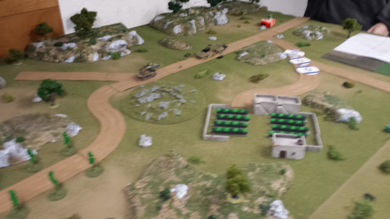 An Israeli Magach and two Zeldas advance down the road while unknown Israeli forces move on the walled orchard.