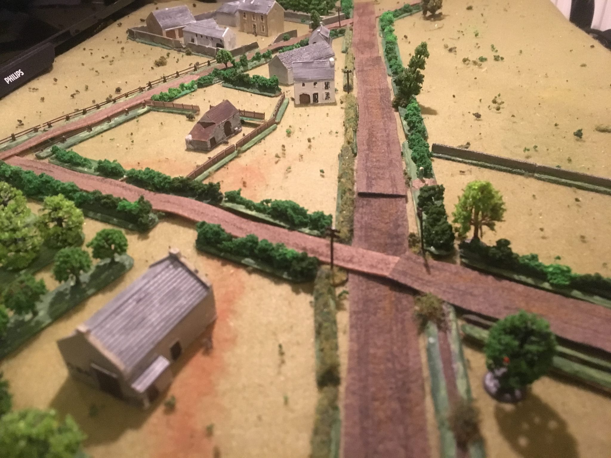 A view from the British end of the table showing the main road and the large walled farm complex in the distance.  The British plan was to push two platoons up:  No 1 platoon on the right from the orchard, and No 3 platoon cautiously up the main road. A section on the right would cover the open fields beyond the low wall.  The Universal carriers with Vickers MMGs and 75mm armed Shermans would provide support. The Firefly with attendant 75 gun Sherman would stalk any German armour.  No 2 platoon was held in reserve in the middle.