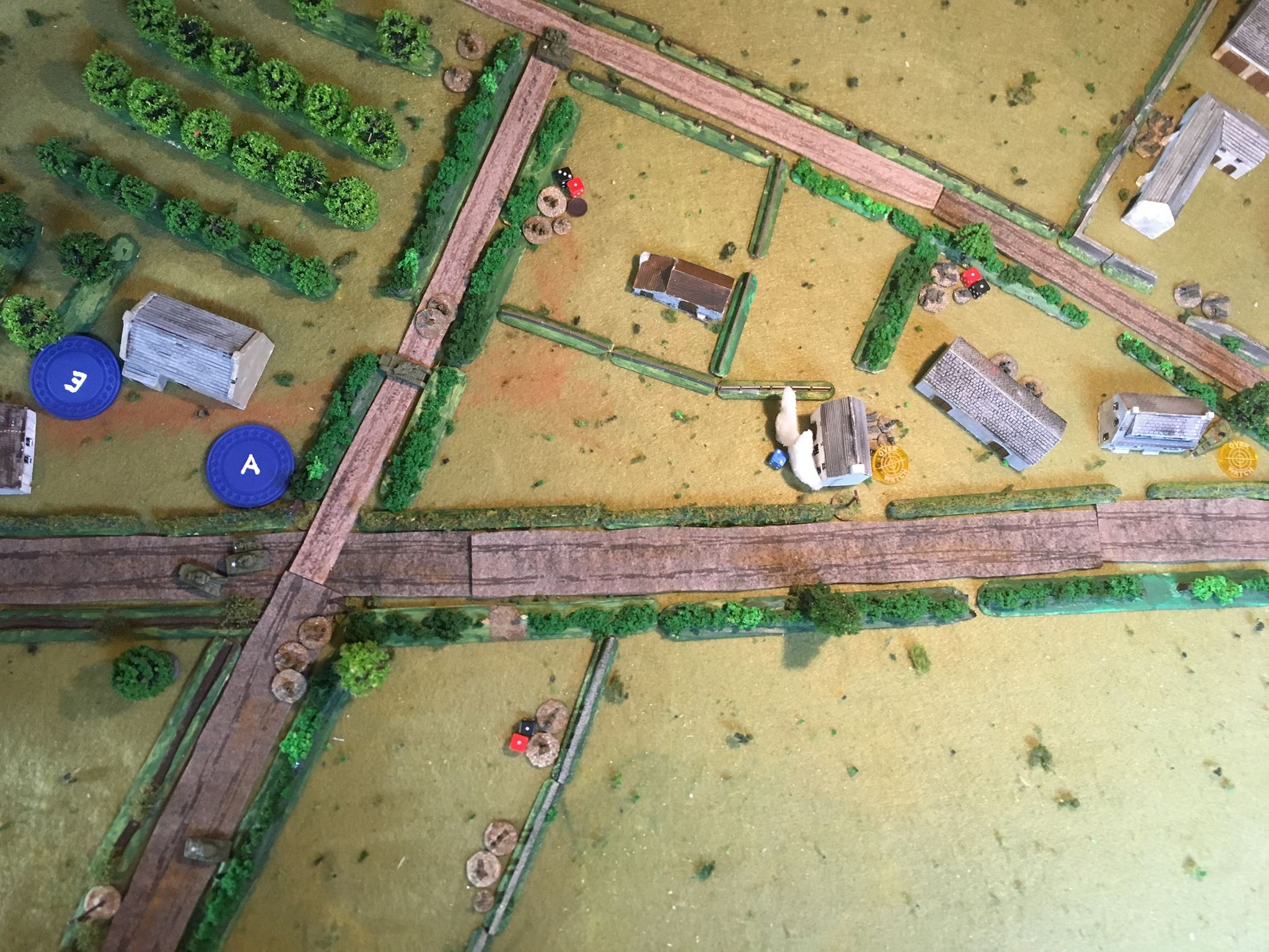 A section from No 1 platoon try and dash into the dead sniper's hiding place but get shot at by a Germans squad from No 2 Zug behind the thick hedge opposite.  Sections from No 3 platoon take fire as they shelter behind the wall.  In the centre, the British bring up their secret weapon - a Churchill AVRE - to demolish the German strong point.