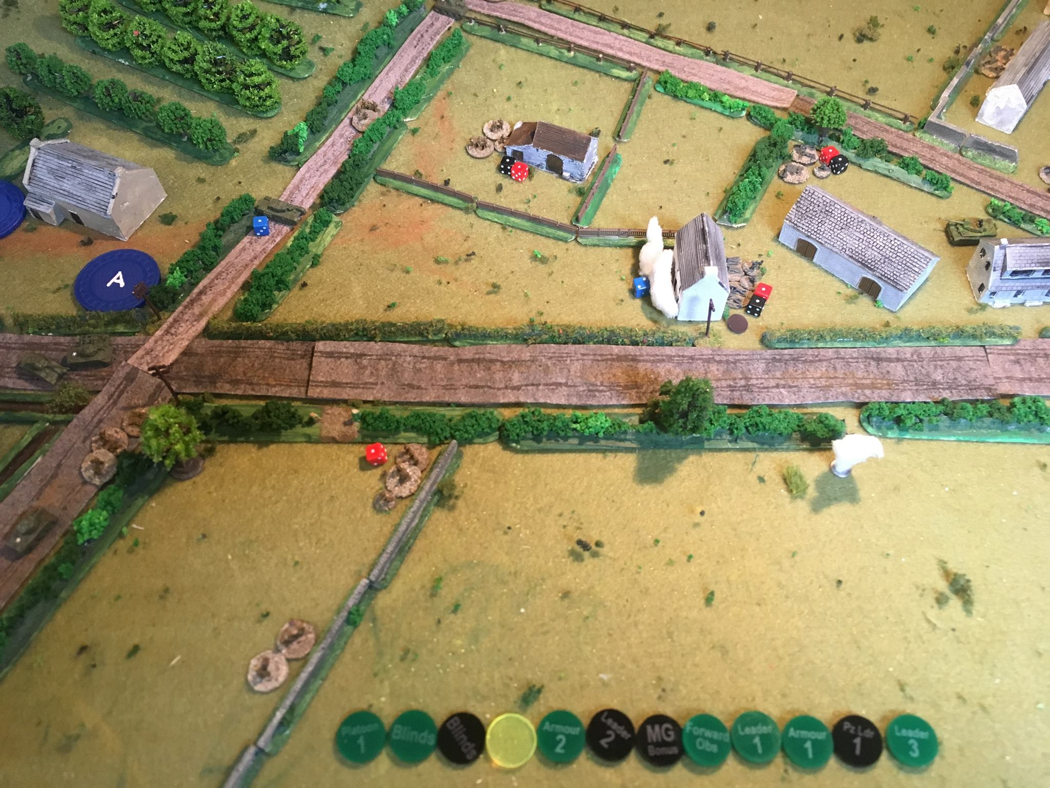 "A longer turn. More smoke is dropped in front of the house. The petard fires and the Germans are lucky to escape lightly. The Tiger moves up from its hiding place to engage the AVRE which, if left alive, will demolish every building in the village. Do those things really carry 31 rounds?   The British FOO tries to bring down fire from the mortar battery, but it scatters badly – see smoke from the white spotting round.  The fluorescent chit was for random events from the TFL Special. Came up a few times but only activates on 5 or 6 and so only a 'Medic – both sides may return one ""killed"" man to a section or weapons team of their choice' occurred."