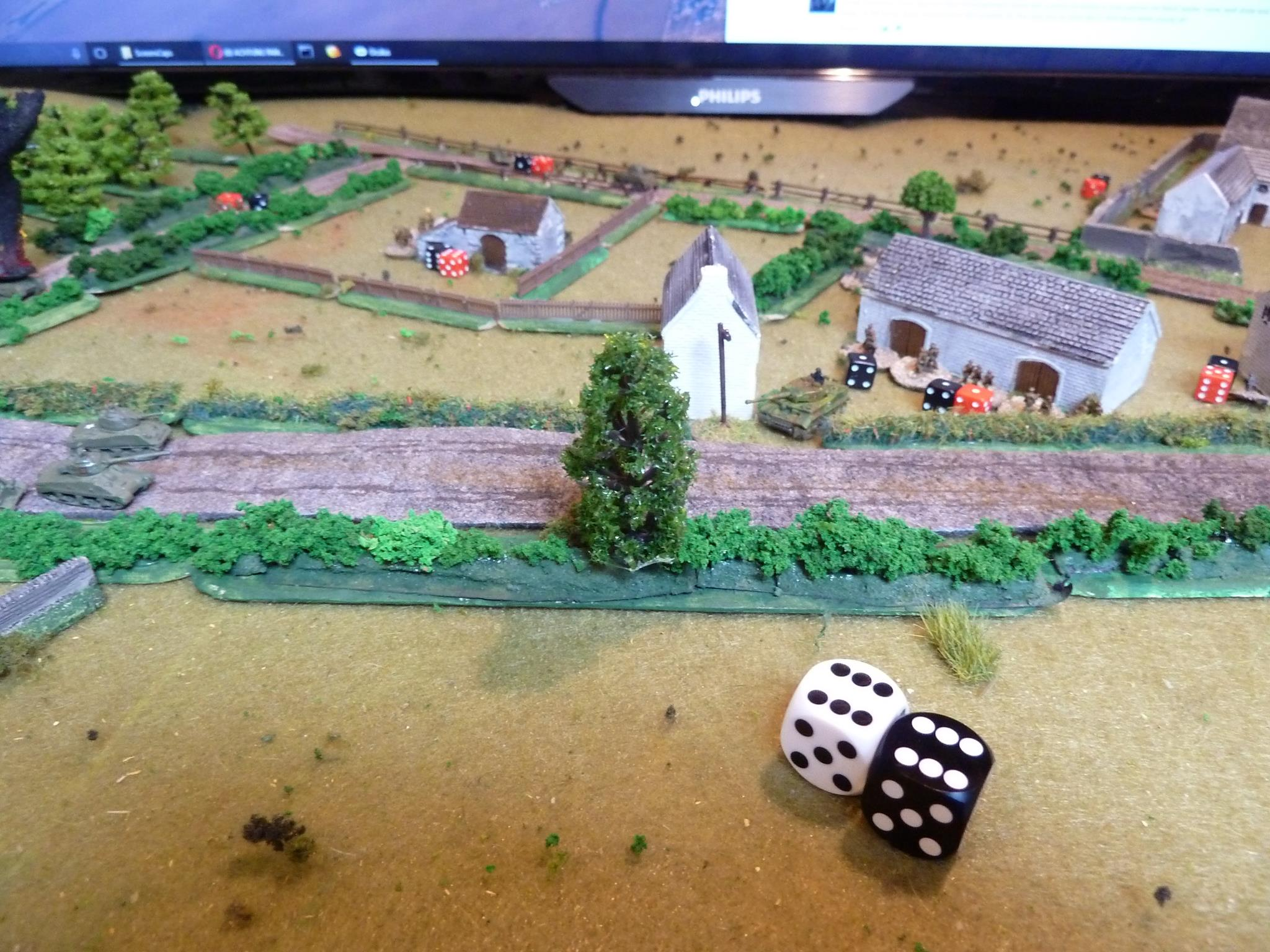 The Tiger's luck is in and it gets to move before the Shermans. It trundles around the stables and edges around the house in the centre. It pokes its nose out, just enough and with one remaining Action gets a shot at the Firefly...and rolls a double six! Critical hit!