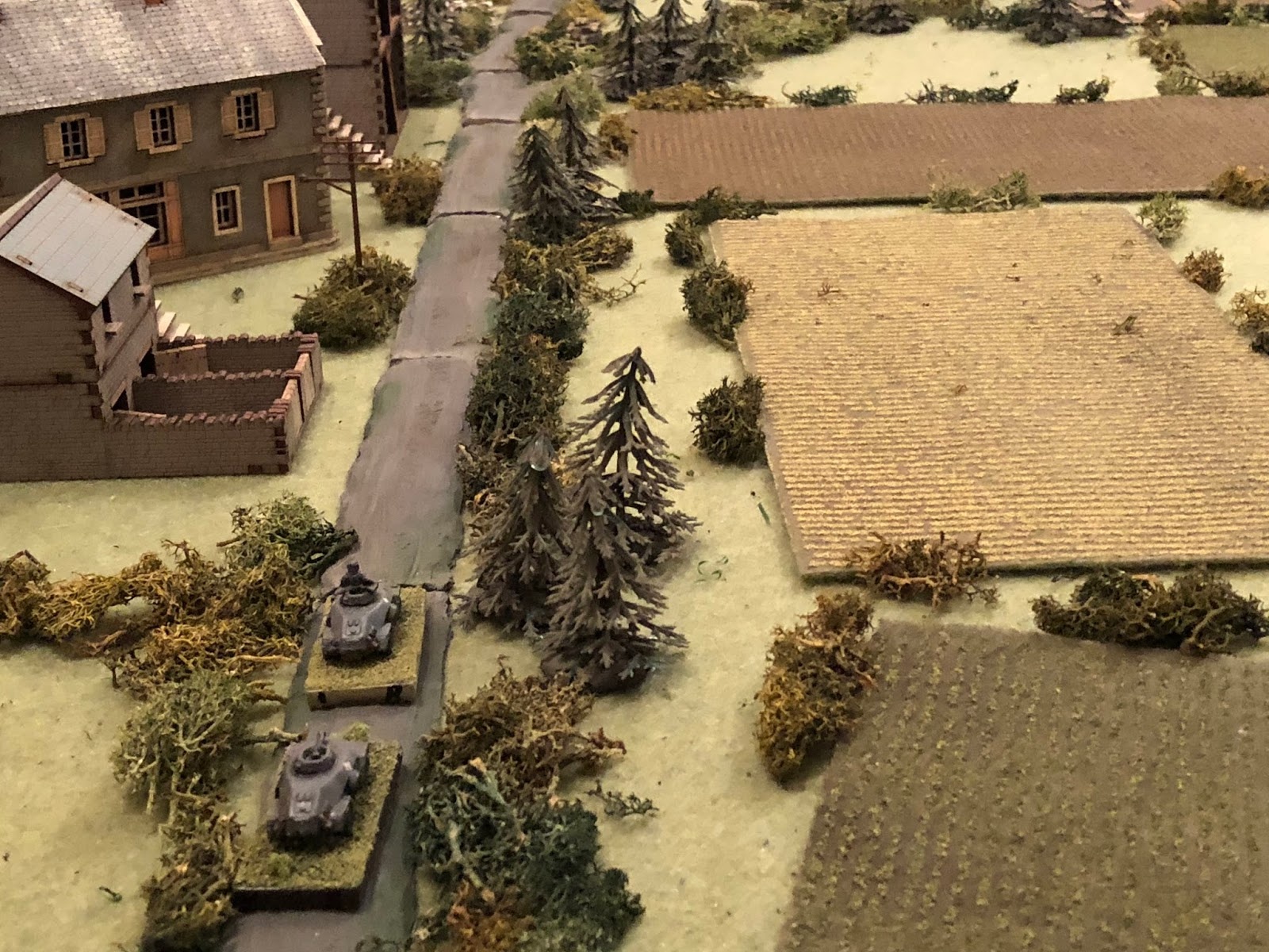 Hearing the reassuring roar of Panzer III engines coming up on his right (off camera to bottom right), Lt Weidner and Cpl Edst cautiously advance their armoured cars up main street, almost reaching the Granary (top left).  Lt Weidner spots something up ahead and calls a halt...