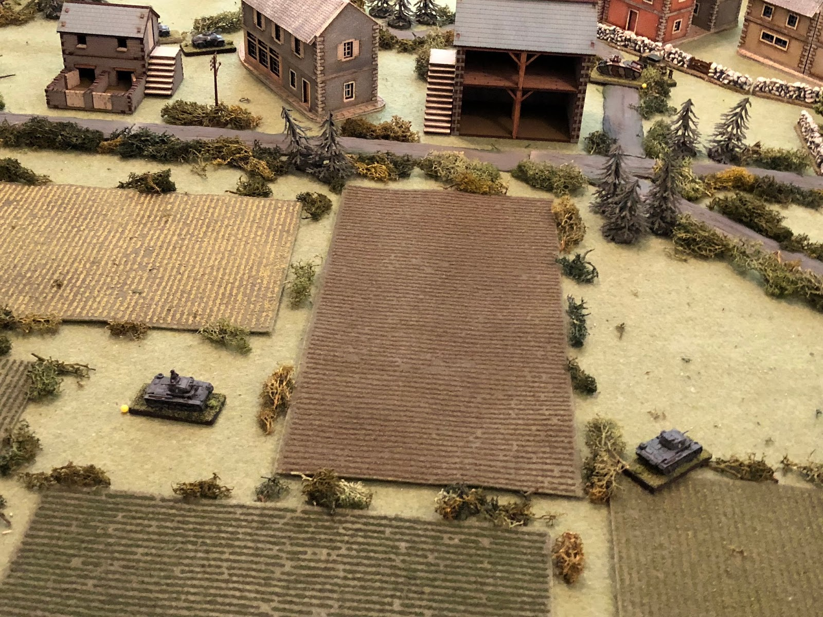 Sgt Mayer thinks he's going to get on the flank but his tank bottoms out in a rut in the field (bottom right), significantly slowing it down, while Lt Loeb's driver (left) appears to be having problems manipulating the transmission, as they don't move very far either...  *the beauty of dicing for movement! It's awesome!