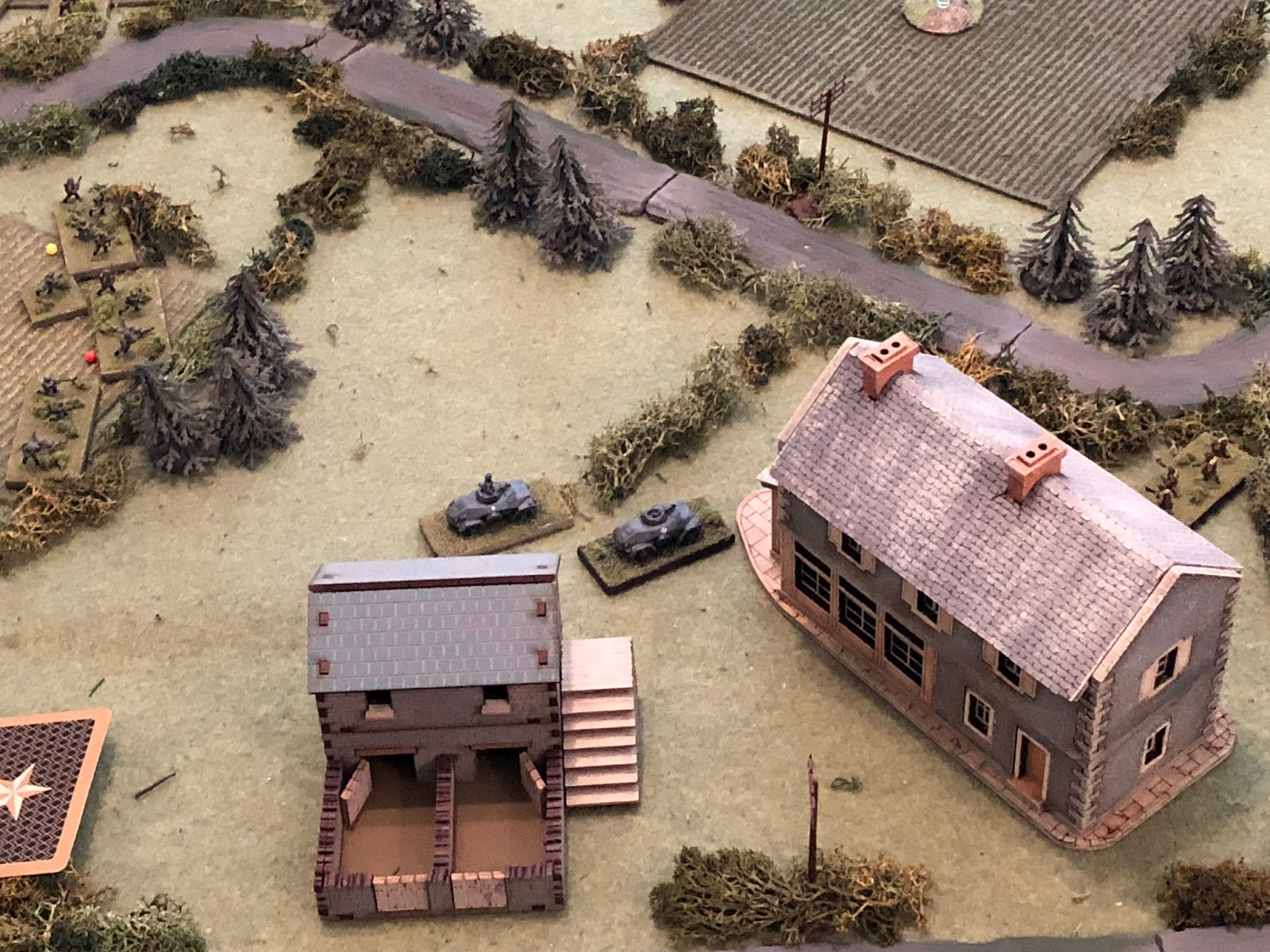 Lt Weidner (cente, with Cpl Edst's vehicle to his right) continues to watch the ville (off camera to top right) and, every now and again, pump 20mm rounds into it.  But suddenly he spots movement directly in front of him, just on the other side of the Granary (far right)!!!
