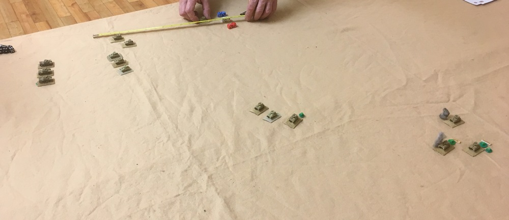 """This shows the action after about four turns.  The Italians have two troops of tanks on table, and the British have made a rapid advance down the table with the light tanks. As a result one troop has already been knocked out in the centre of the table.  To be able to call in the British reinforcements, the initial forces were required to spot all on table Italian tanks, get at least one troop beyond half way down the table and lose at least one tank. At which point the off table HQ would believe that the Italians were actually attacking!!!!  The British are in the middle of what would be a futile and expensive emulation of the """"light brigade"""" and have charged the Italian tanks to get the maximum effect from the HMGs. The result was some minor damage to the Italians and, eventually another four light tanks being destroyed"""