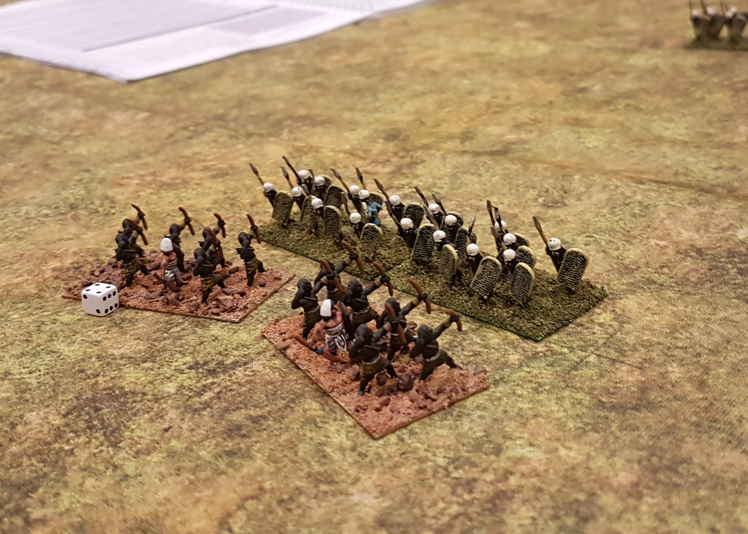 Formed and disordered units for TTS, along with a dice to mark ammo. Note grid intersection just to the right of the ordered spearmen.