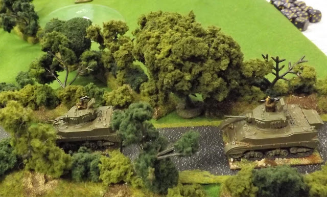 The British tank commanders nervously concentrating on scanning the nearby hedgerows with fingers firmly on the trigger