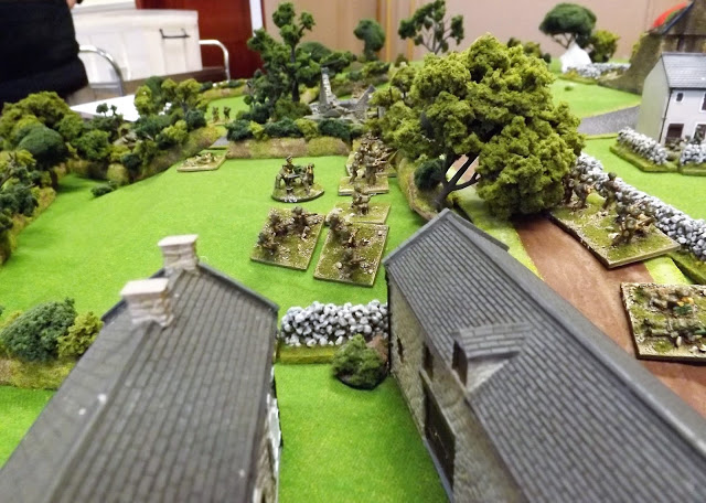 With British troops manning the hedges and walls along the lane German artillery and a lone sniper firing from the roof on the right open up on the British and their command team