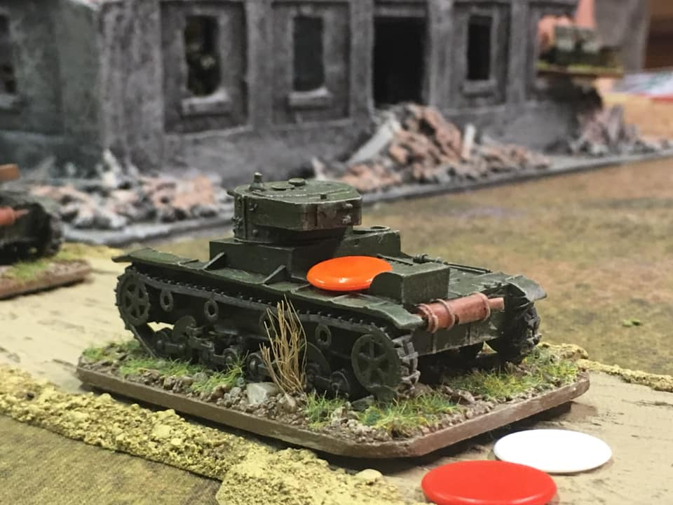 T26 struck by a Polish AT gun firing from the far corner of the building. Shock red, loss of one action dice white, buttoned down orange marker. This vehicle certainly went through the Mill tonight.
