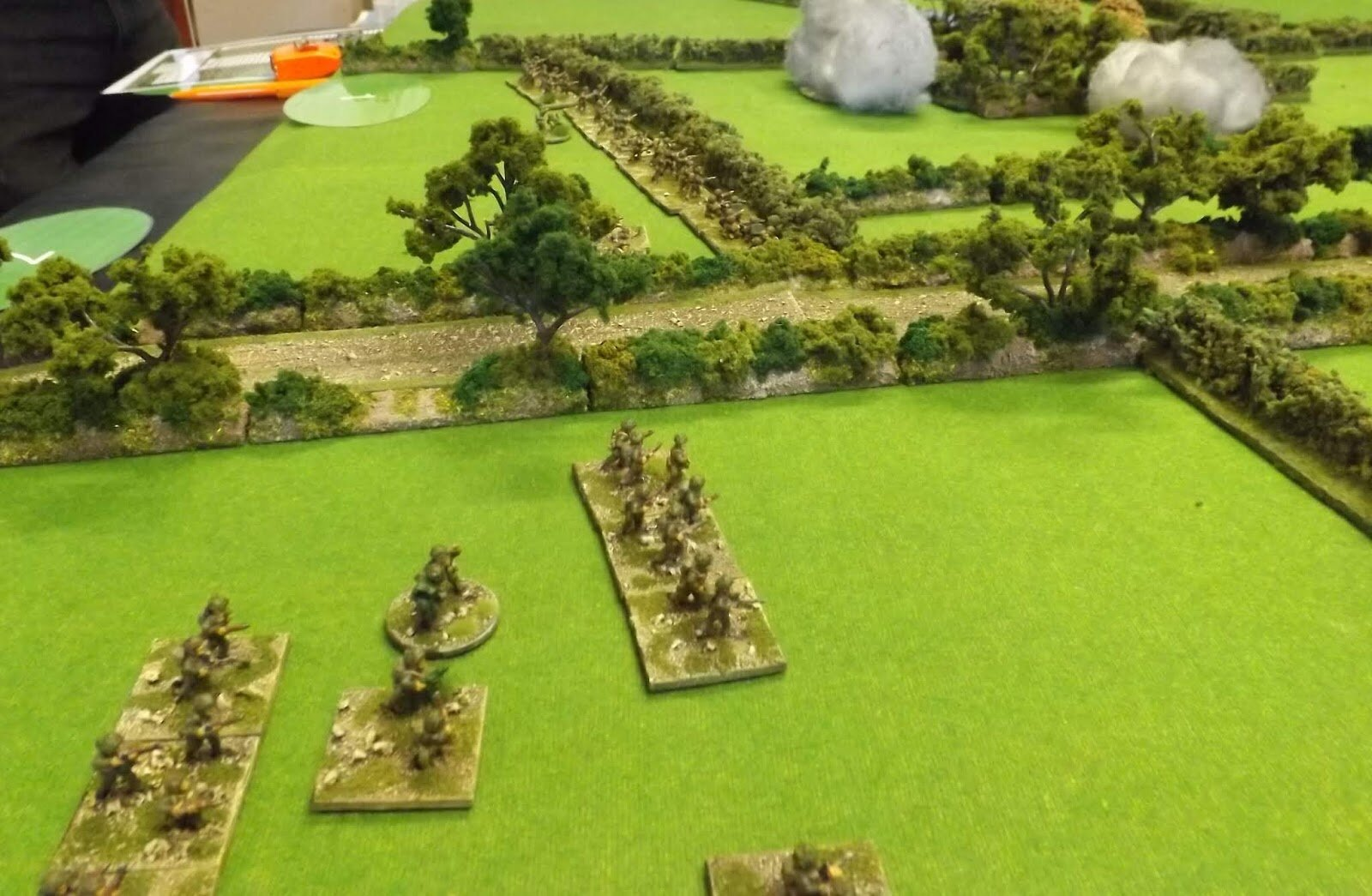 Troops lining hedgerows provide a fire base for those crossing fields trying to find the flank