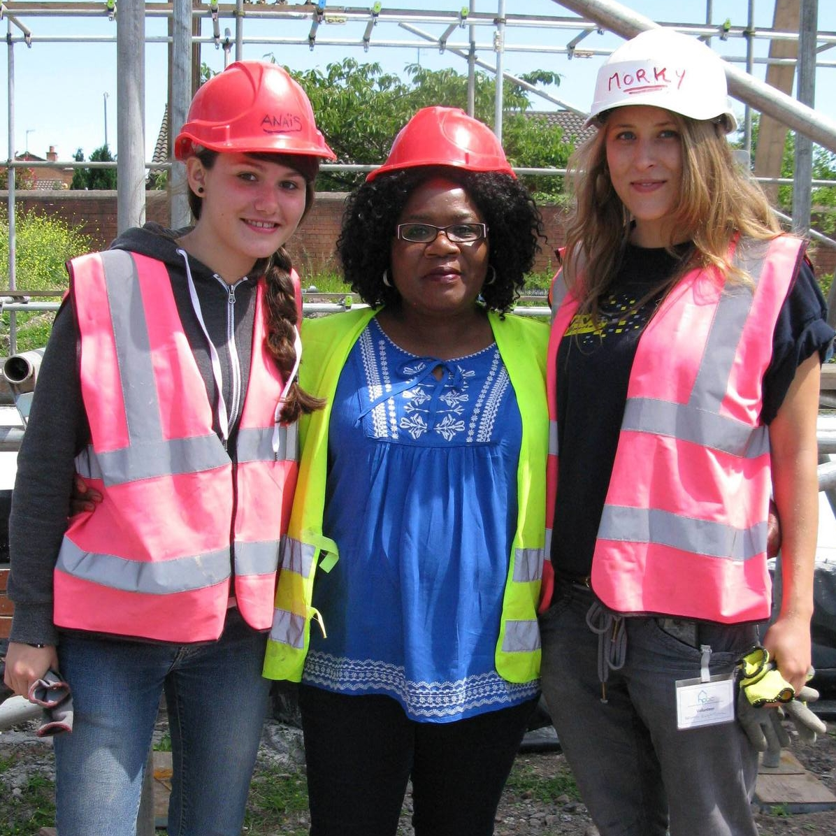 HPBC's homes are built largely by volunteers, including the home partners themselves. Home partner Joyce Msiska (ctr) with two French students currently volunteering on site, Anais Lameira (left) and Angelique Brouard.