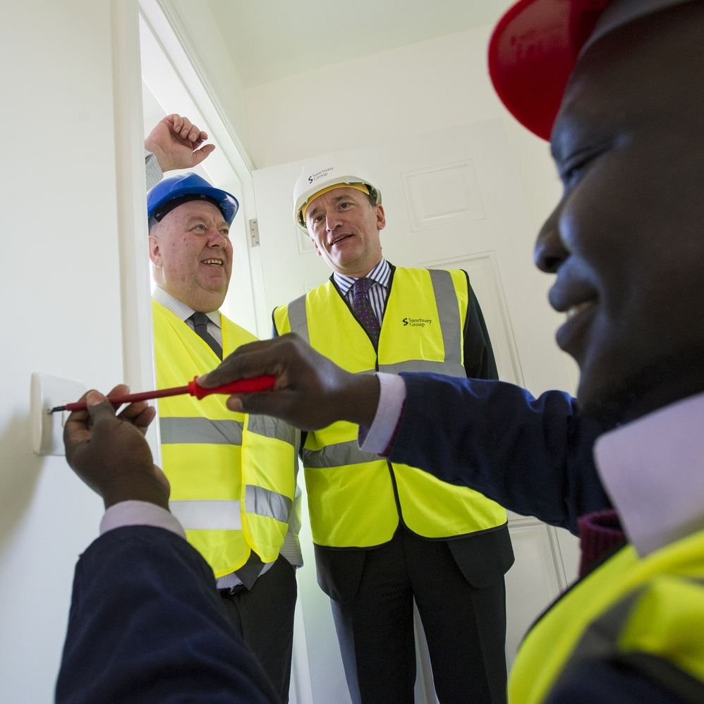 Mayor Joe Anderson and Sanctuary's chief operating officer Ian McDermott look on as City of Liverpool College student Mani Mango undertakes some electrical work.