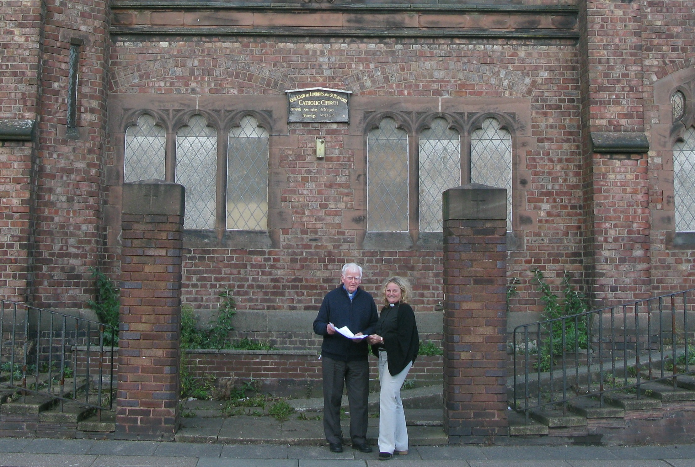 Father Peter Morgan and HPBC chair Shannon Ledbetter review the plans