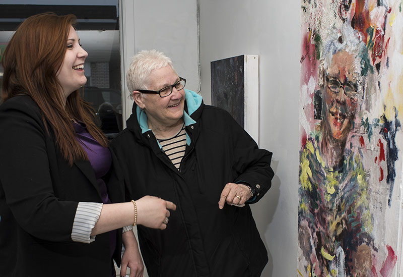 Reflections: Local Artist shares a piece of her thesis exhibit with her Grandmother and subject of photo during her opening Thursday evening.  Foggs work shows reflections on relationships and influences and are mixed media panels depicting family and friends.