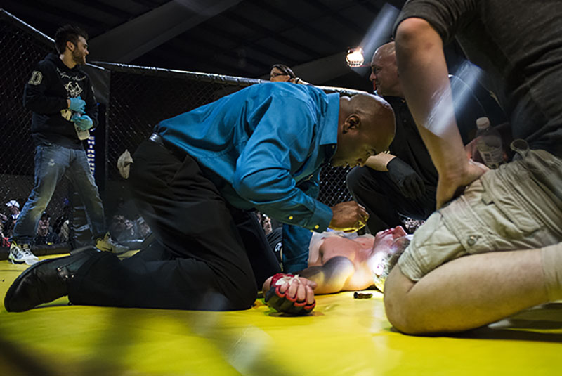 Ring side Doctor is called to the ring after fighter loses bout by knock out.