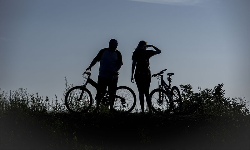 Summer Nights: Lee Maines and Kristin Miller take a few minutes fromtheir bike ride on South St. Mary's Island totake in the view from the westside looking towards LakeSuperior Saturday July 25, 2015.