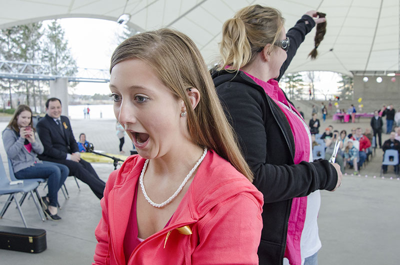 Cut to Cure:  Paige Furbacher reacts to her new haircut, while Amber Scornaienck who did the honours show the crowd her generous donations the Angel Hair for Kids during the Celebration of Light.  The event held at the pavilion was a fundraiser for childhood cancer and memorial for Chiara Scornaienck who who lost her battle to Diffuse Intrinsic Pontine Glioma a rare brain cancer on August 13th 2014.