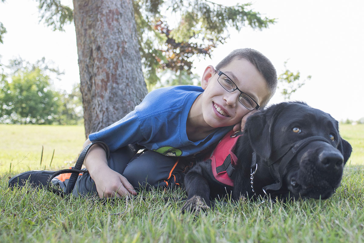 Miguel Bedard and his Autism Guide Dog North take a few quiet moments at Bellevue Park, August 18,2015. While Autism Assistance dogs can help reduce anxiety, difficult behaviour and help to keep children with Autism Spectrum Disorder safe, friendship and unconditional love are ultimately one of the greatest gifts that they bring to their children.