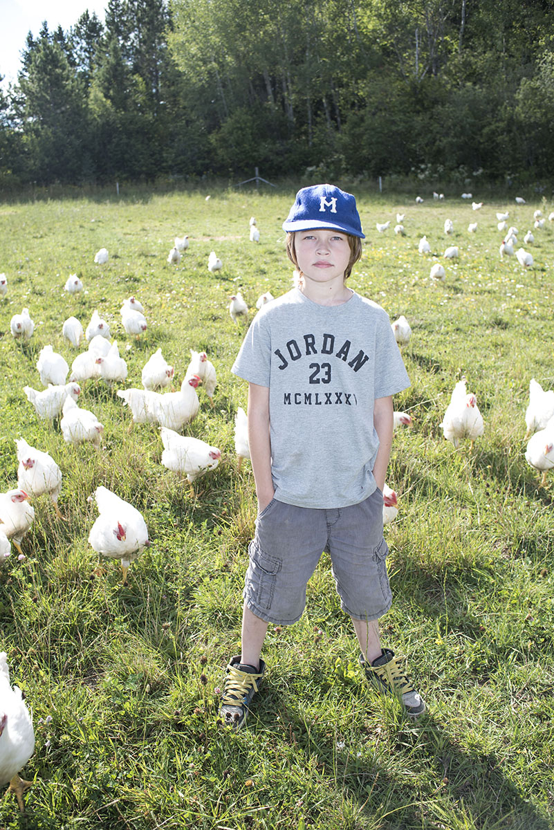 Happy Chickens: Aidan Lemieux, 9, shares the living conditions for the Valley Field Farm free range meat chickens, Friday August, 21, 2015.  Chickenspermitted to free range forage for insects and eat leftover crops while at the same time fertilizing the soil. This creates a symbiotic relationship between the animals and the land.
