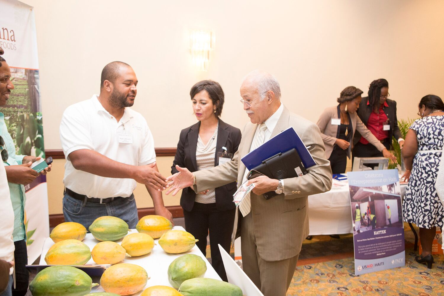 SIENNA Agricultural Holdings is a business that produces high-quality papaya. The booth gets a visit from Robert Labrousse, minister of Haitians Living Abroad.