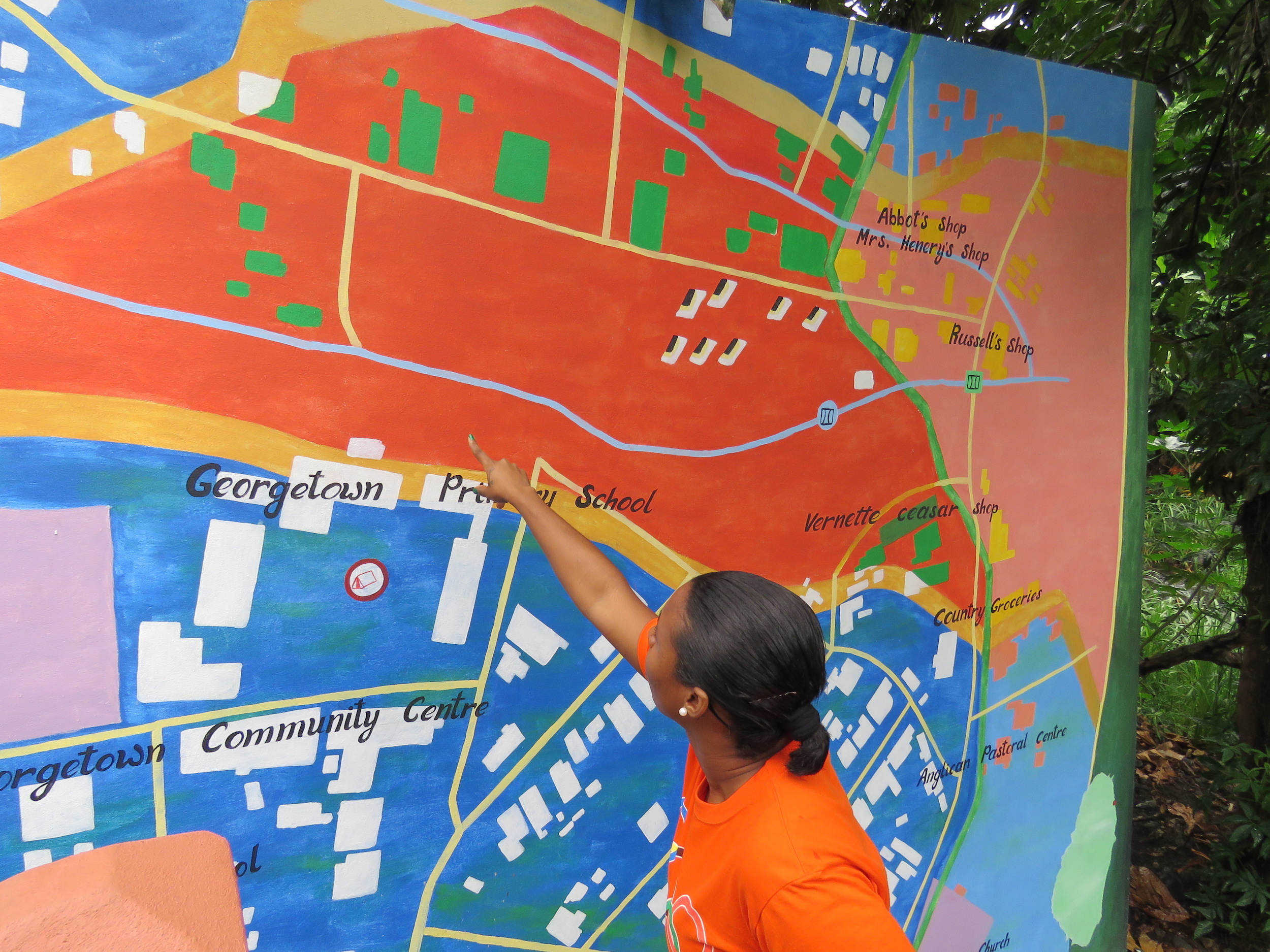 Natalia Bhajan points out vulnerable areas on the hazard map she helped create for her community of Georgetown, St. Vincent.