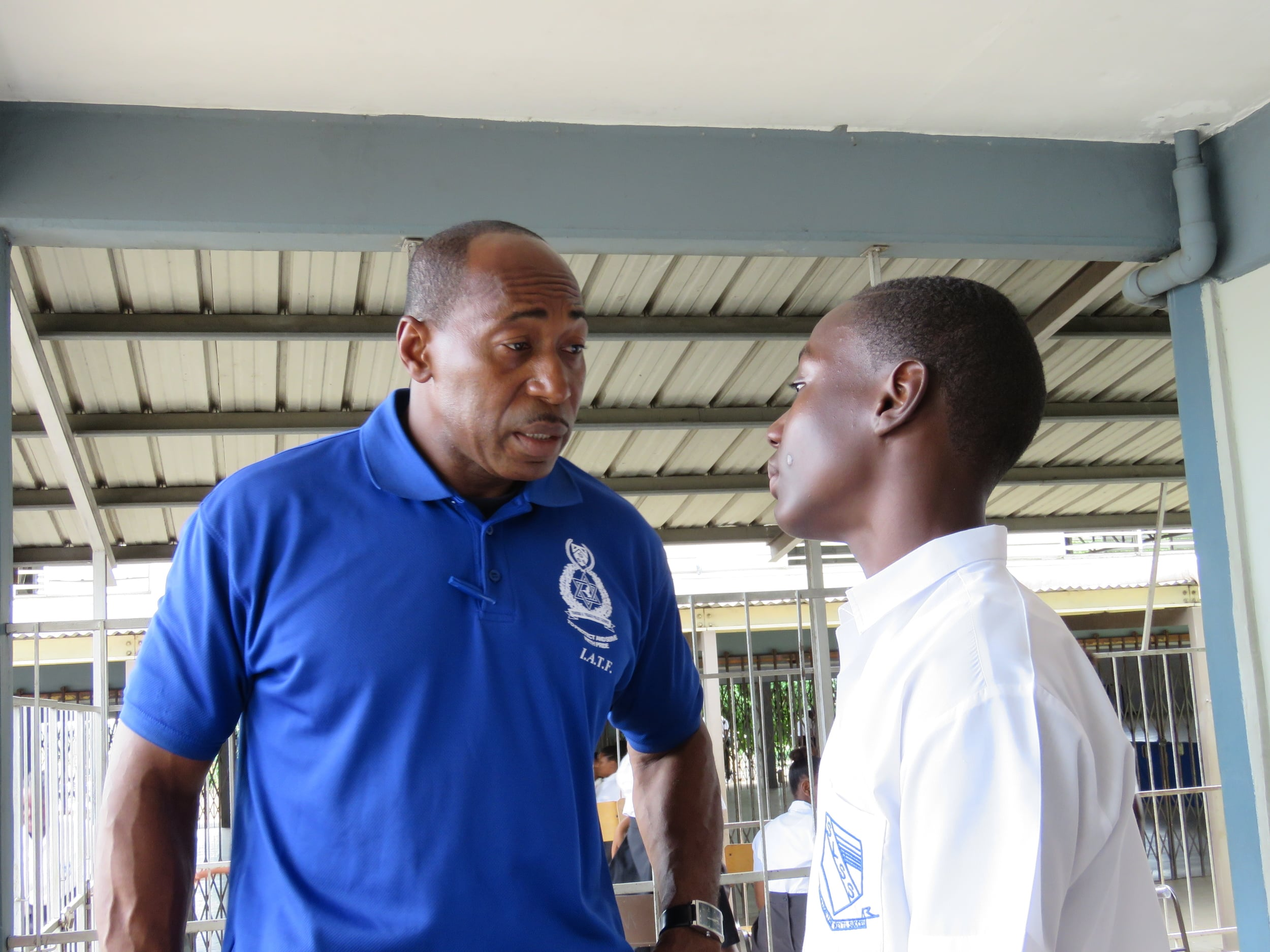 Sergeant Garth Brooks speaks with a student at Laventille Success Secondary School.