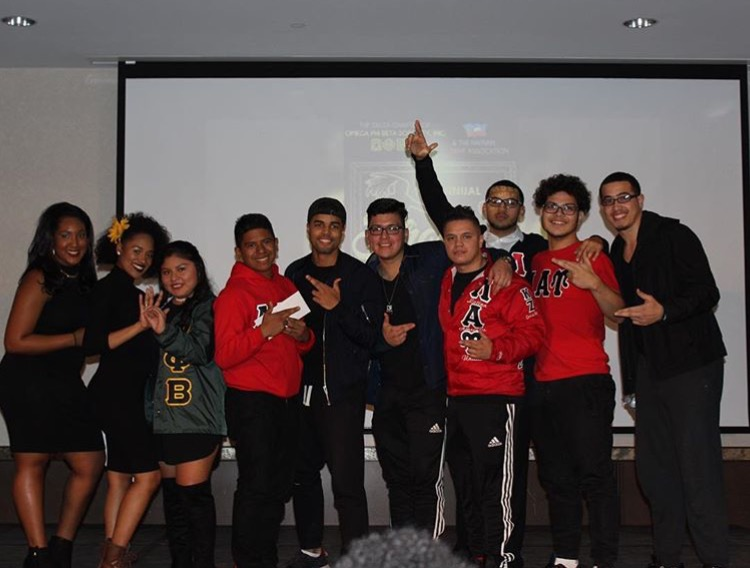 Sisters of Omega Phi Beta pose with m  embers of the Lambda Alpha Upsilon Fraternity, which won the stroll competition.