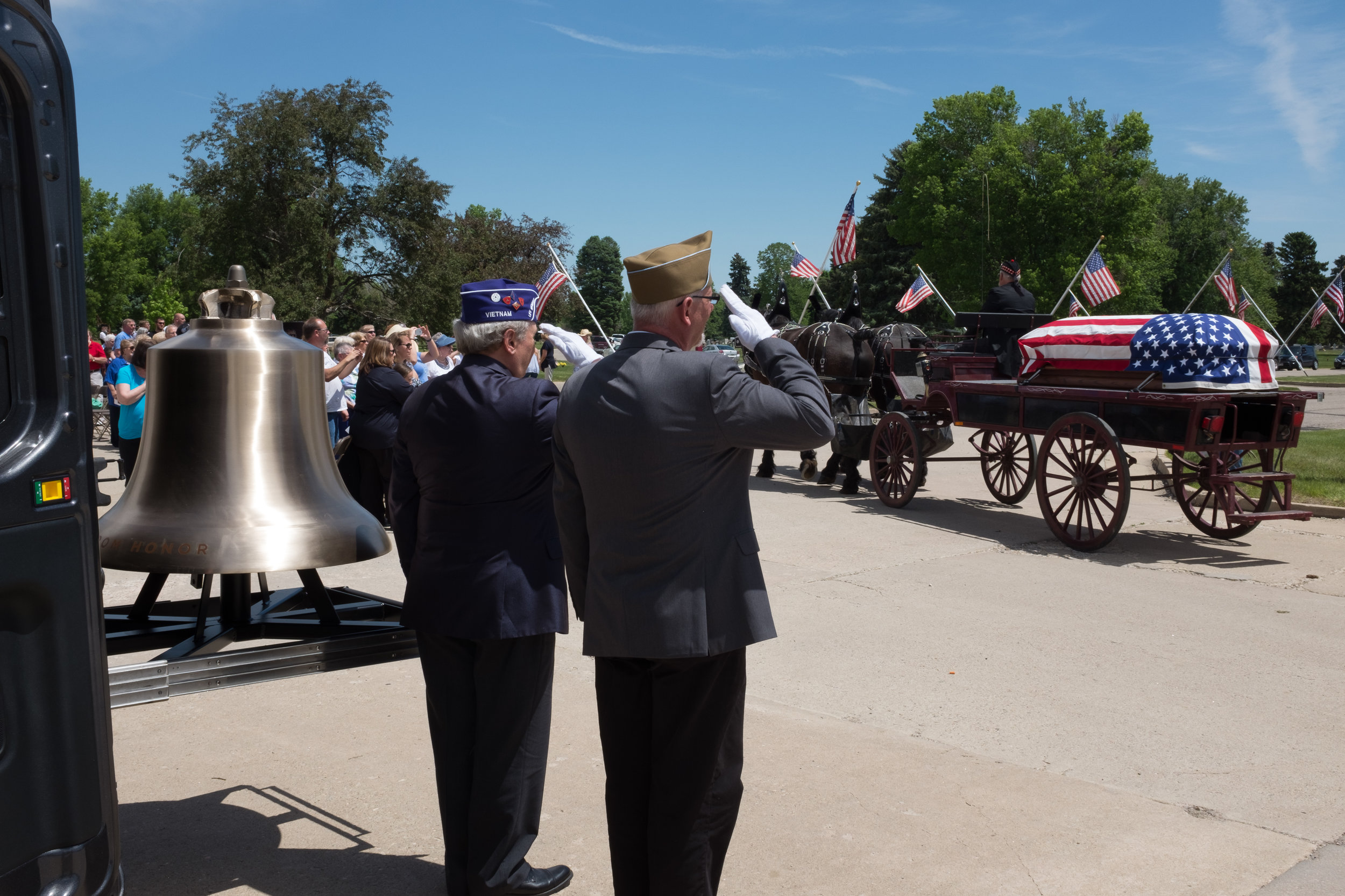 The Honor Bell and Bell Guard, saluting a flag-draped casket on a caisson at Olinger Crown Hill Cemetery during their Memorial Day remembrance in 2016.