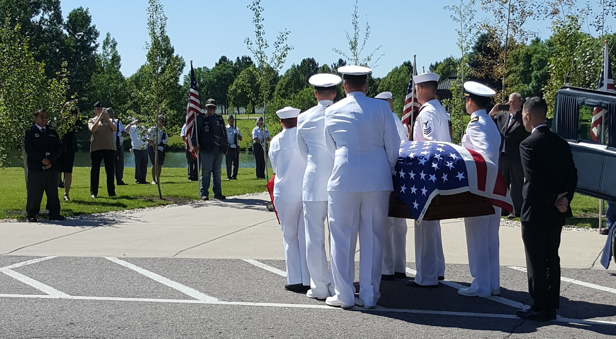 The flag-draped casket carrying the remains of sailor Wallace Eakes is carried by a Naval Honor Guard to a committal shelter at Fort Logan National Cemetery.